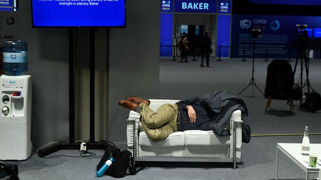 Photo of a man sleeping on a sofa at the United Nations climate conference in Madrid.