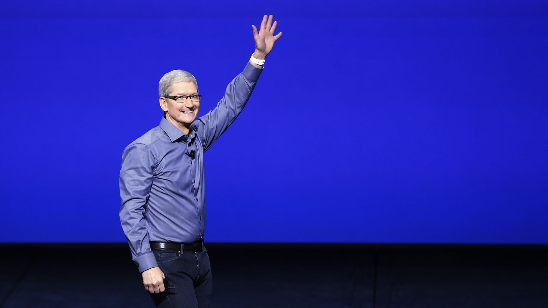 Tim Cook in front of a blue backdrop