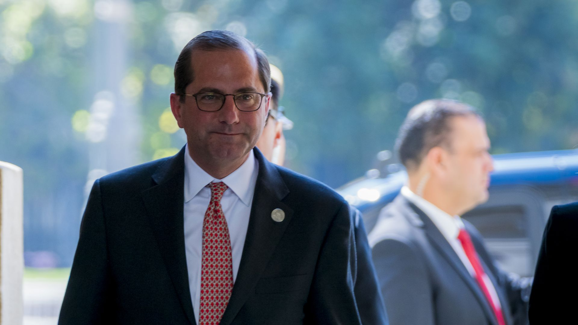 HHS Secretary Alex Azar, walking, with an expression that appears confident.