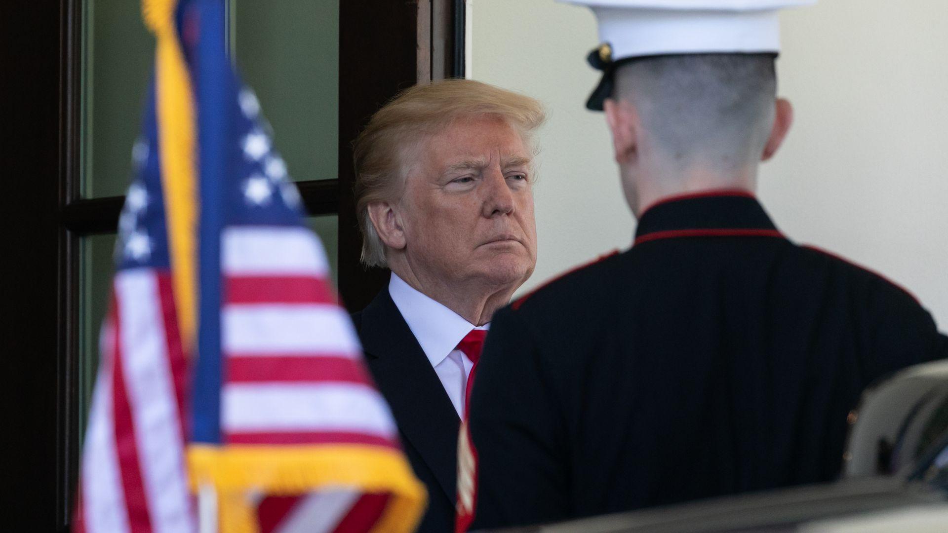 President Trump near an American flag.