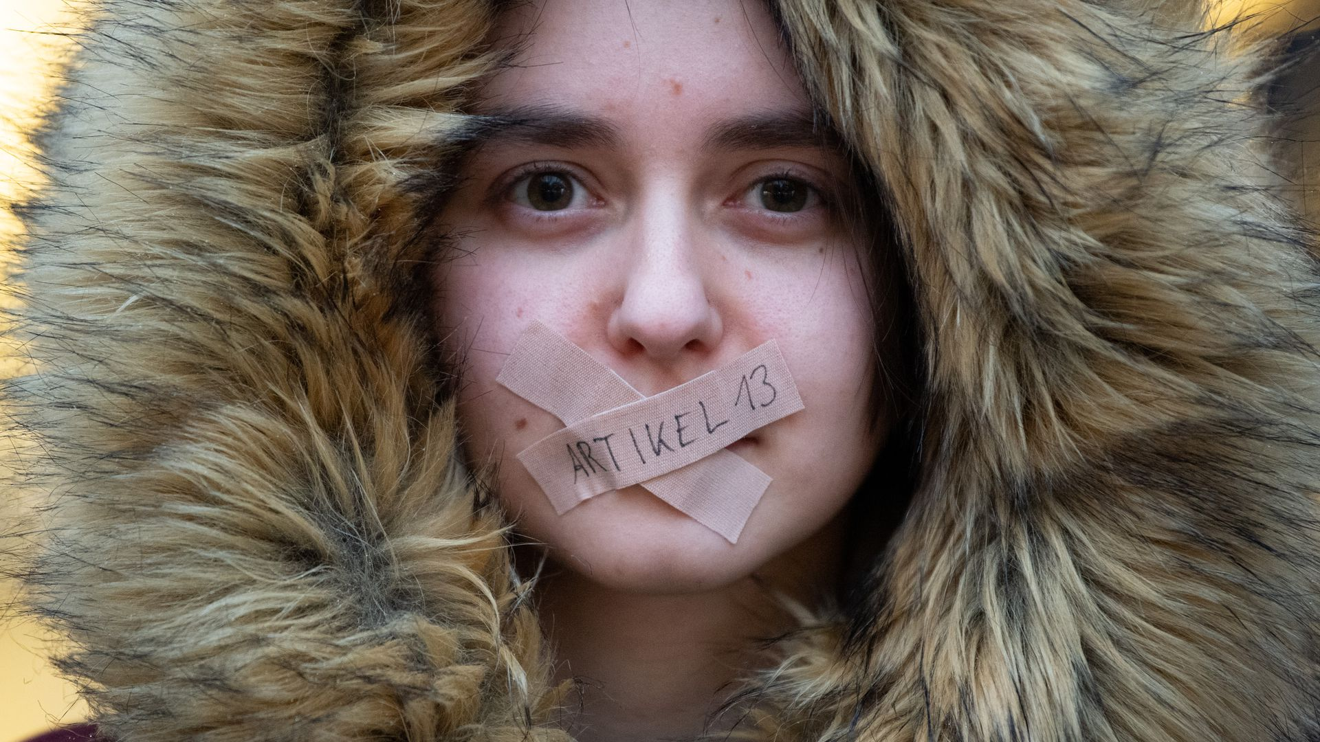 Photo of protester in Germany with tape over her mouth.