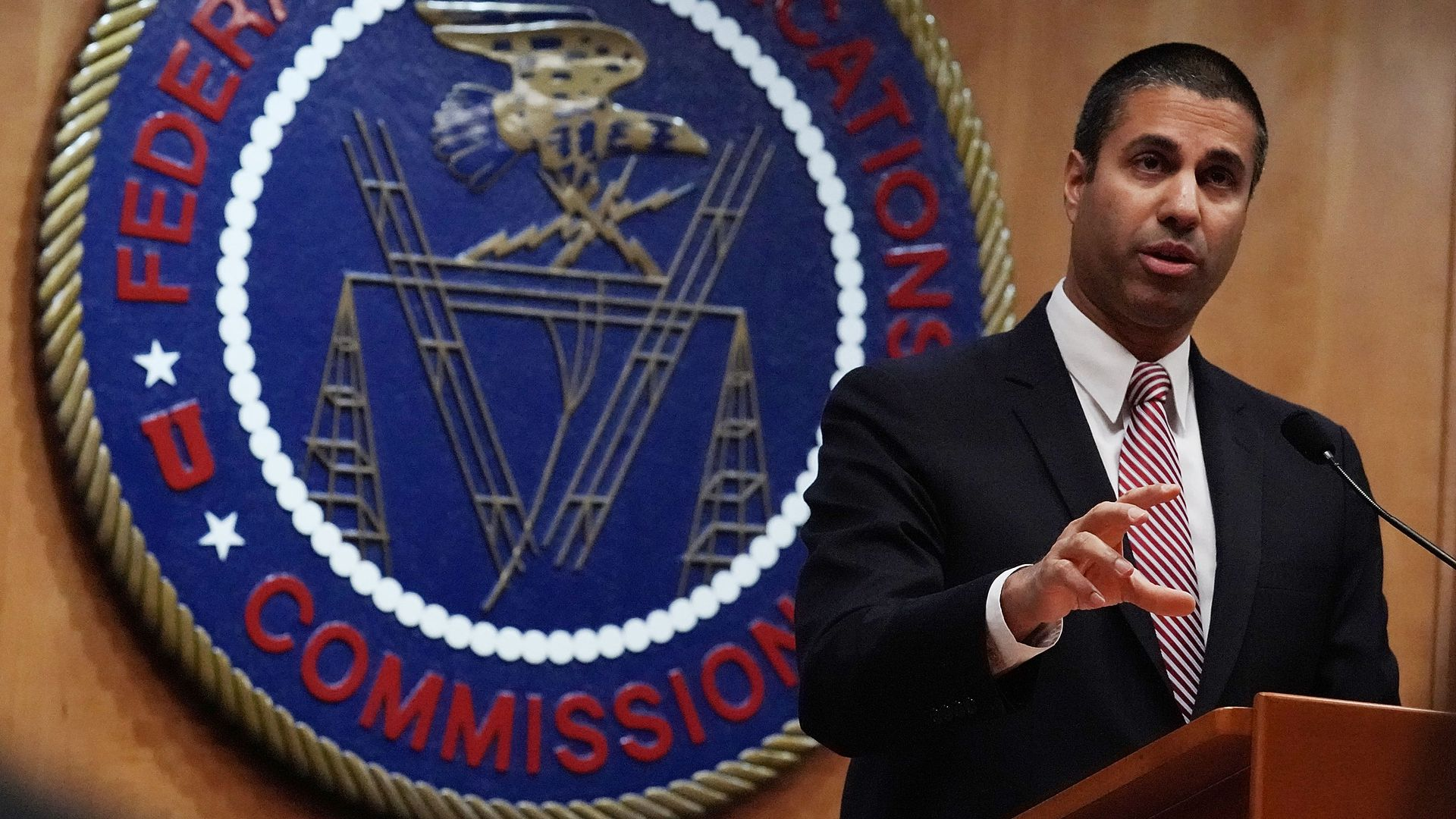 Ajit Pai standing at a podium in front of the FCC seal