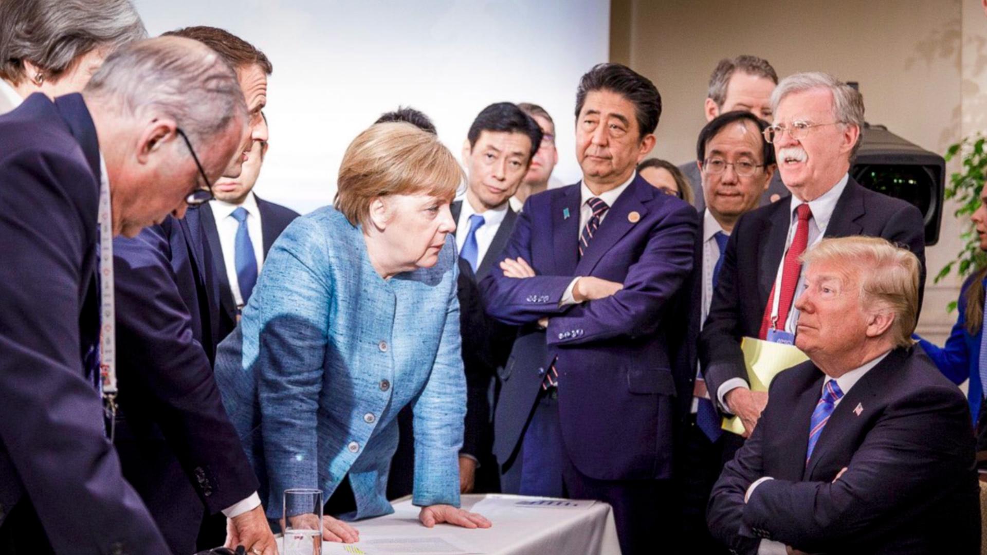 Merkel leans over a sitting Trump