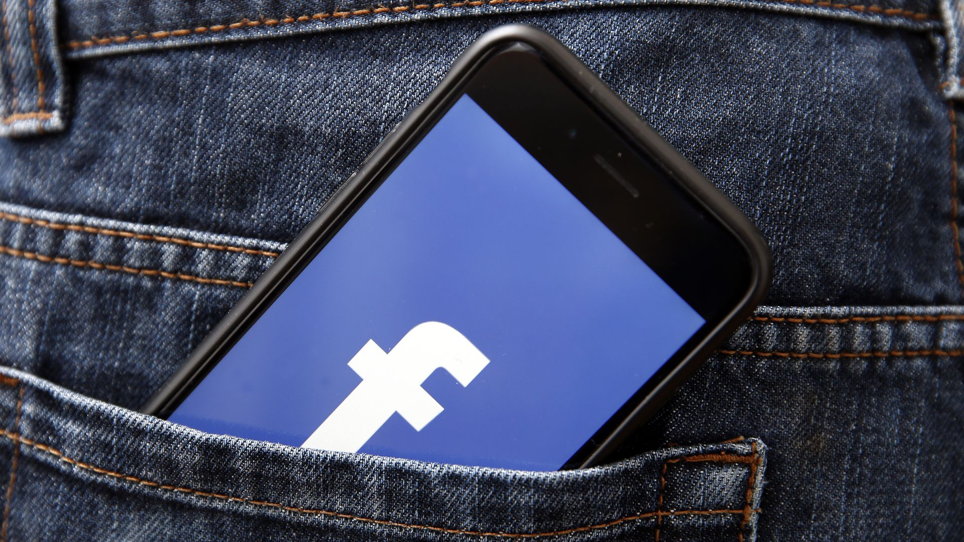 Facebook logo on an iPhone in a back jeans pocket