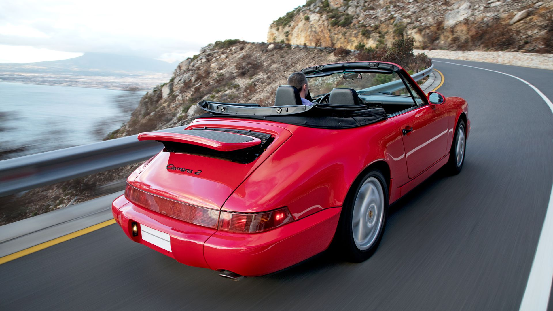 Photo of a red Porsche on a winding road overlooking the ocean