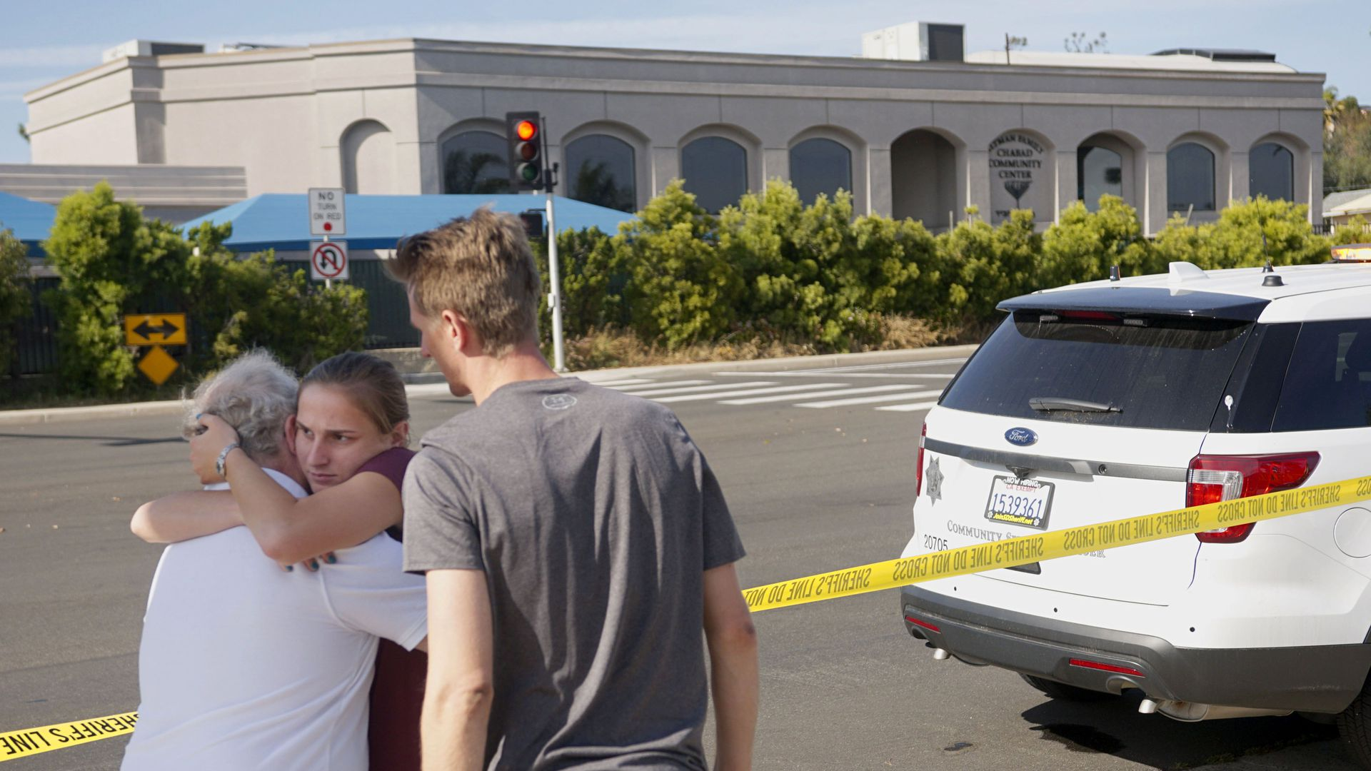 People hug next to police tape across the street from the Chabad of Poway Synagogue after a shooting on Saturday.