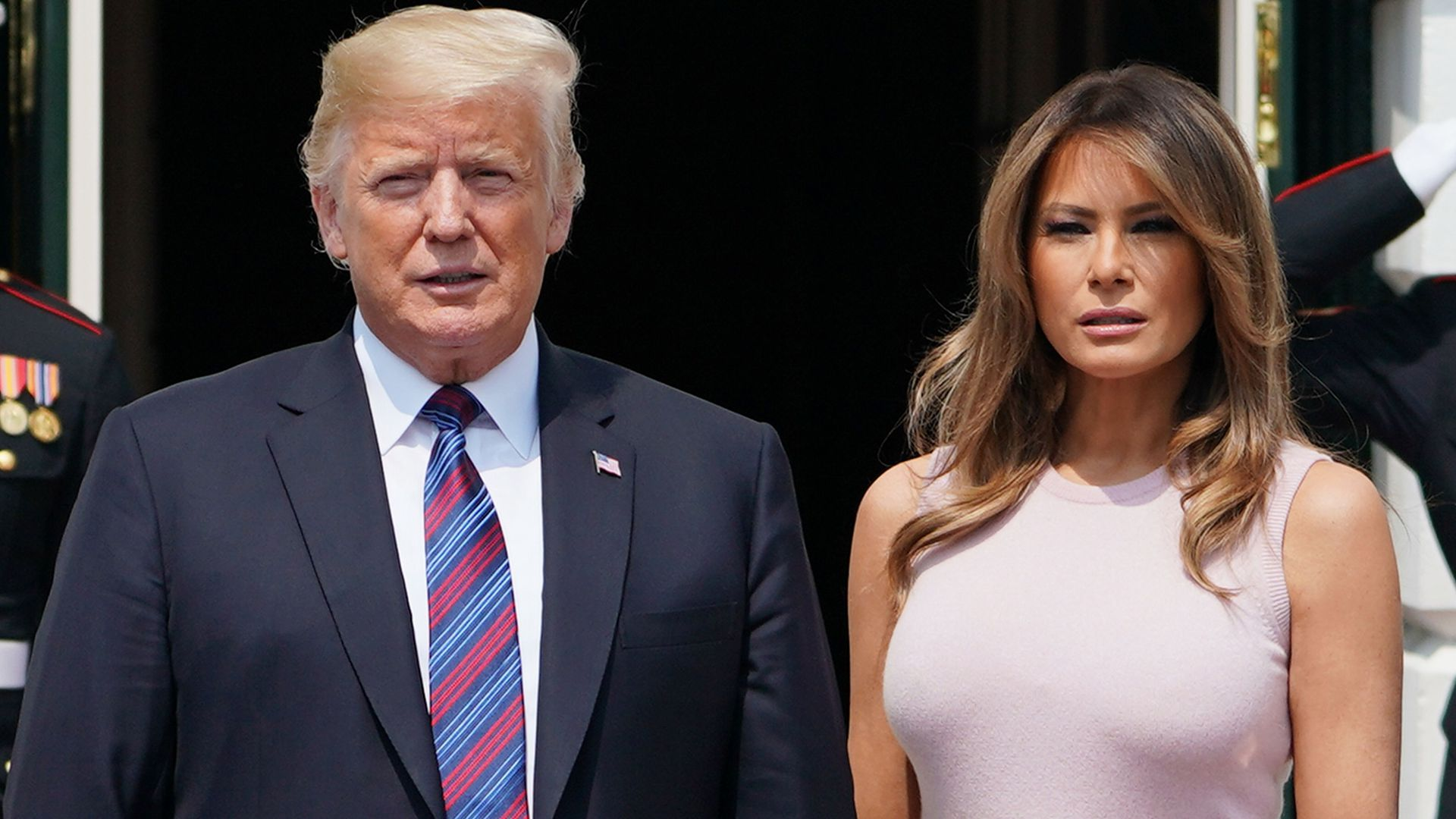 Melania Trump and Donald Trump standing side by side outside of the White House with matching serious, open-mouthed looks on their faces