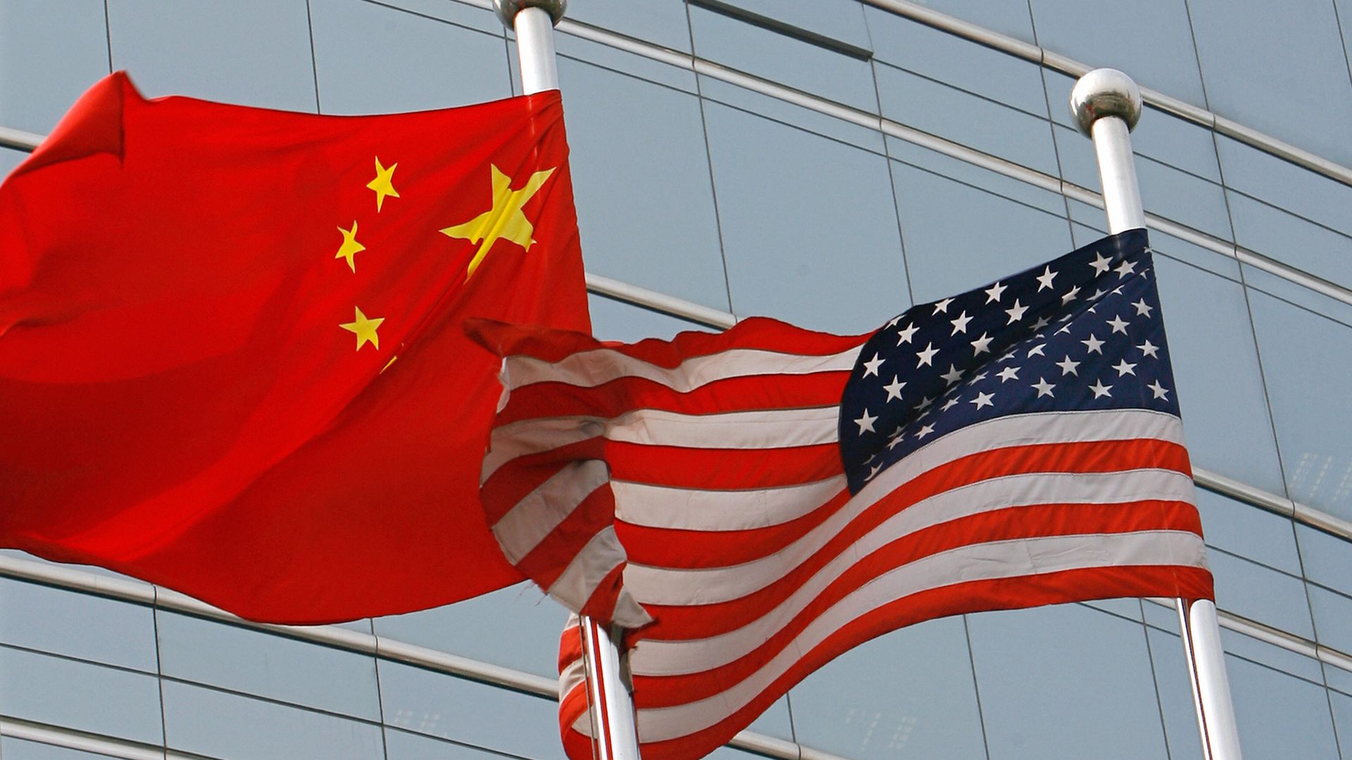 Chinese and American flags waving next to each other