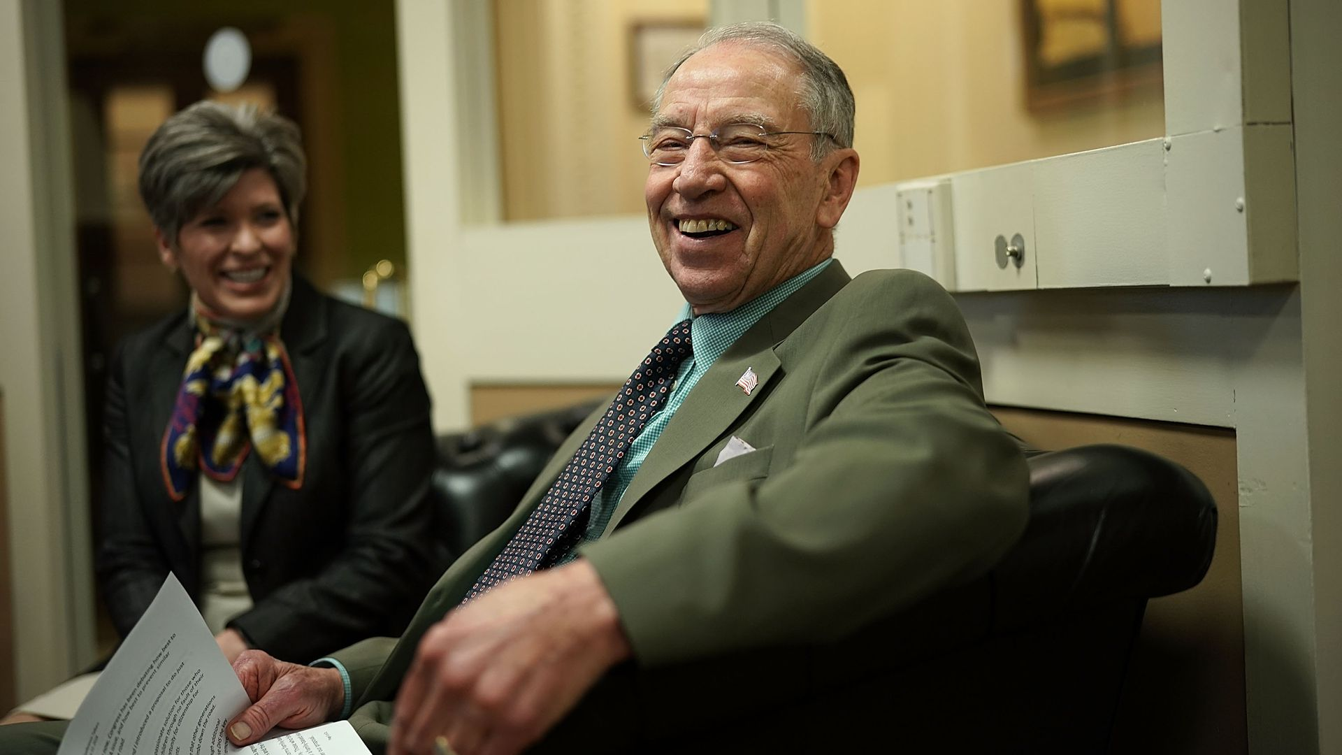 Chuck Grassley sitting with papers and laughing