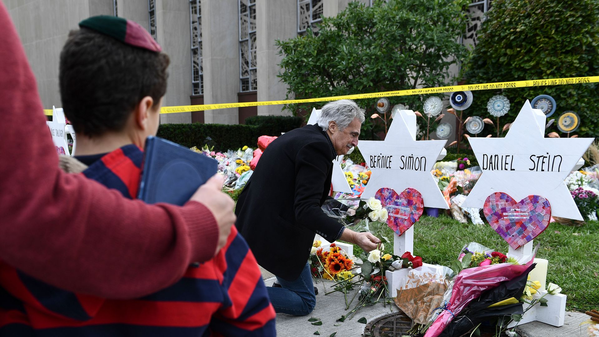 In this image, a man lays flowers at memorials for shooting victims, outside.