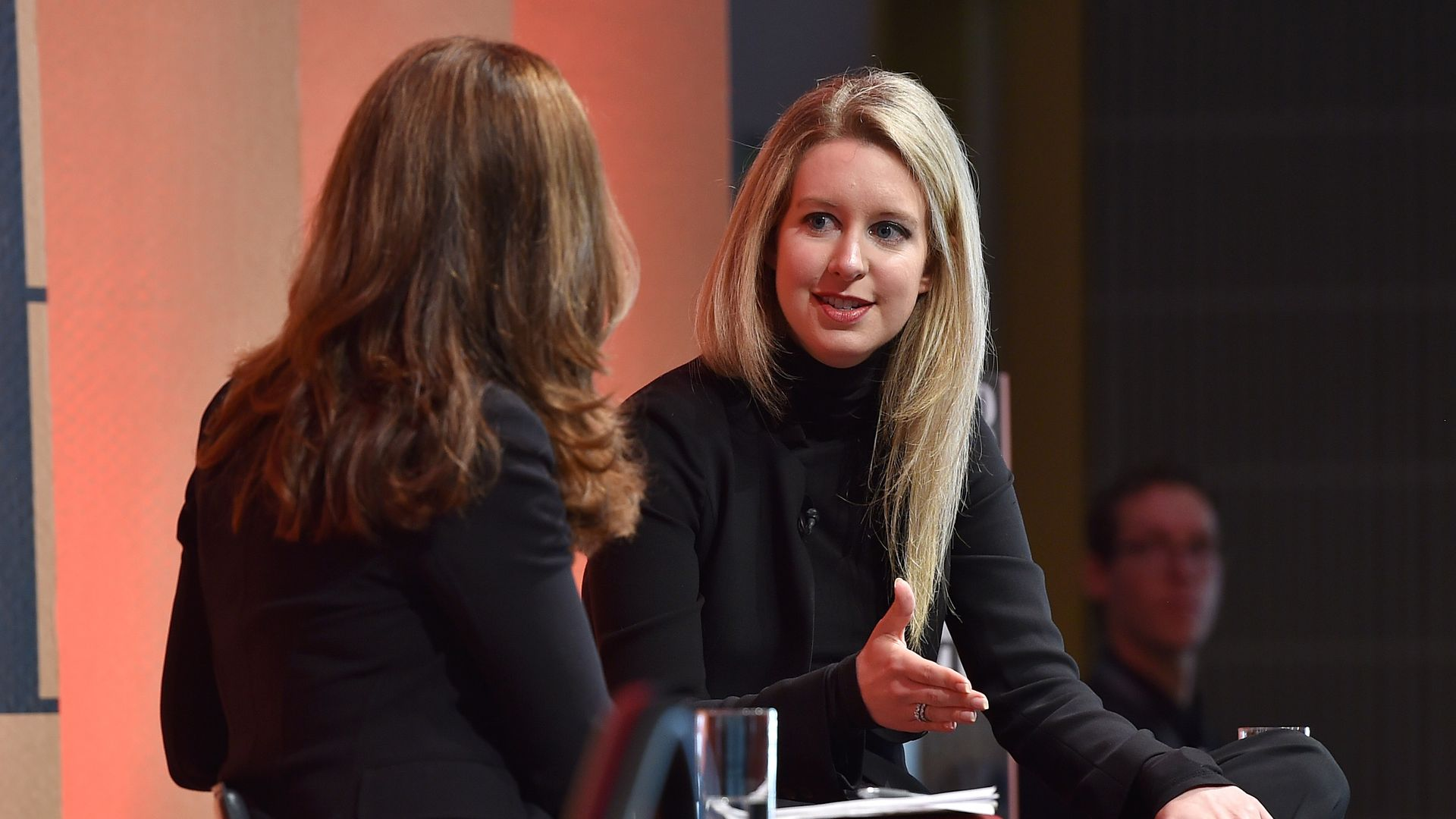 Theranos Founder and CEO Elizabeth Holmes speaks on stage in a black turtleneck.