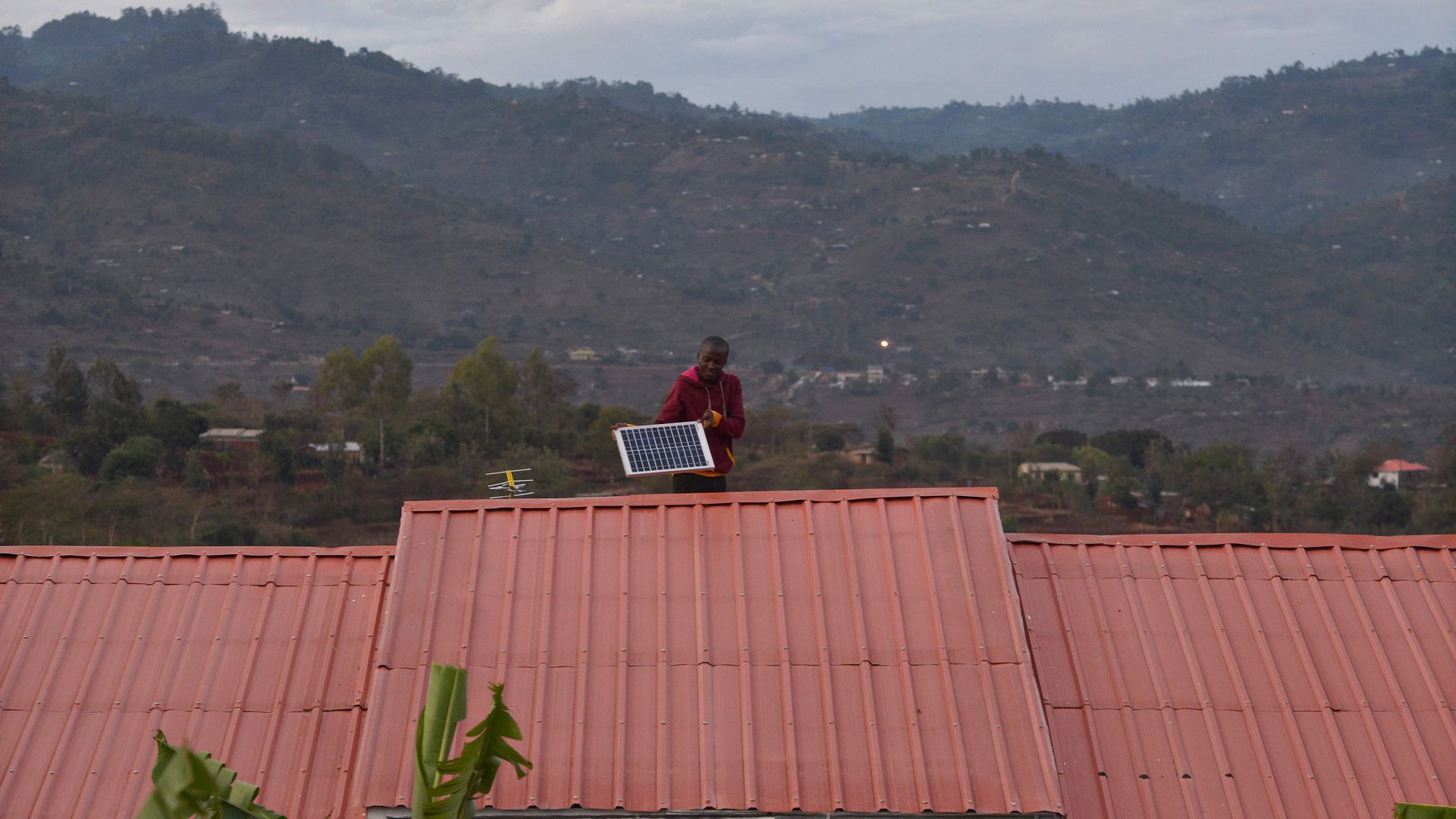 A man adjusts a solar panel on his roof at dusk in the villqge of Kwa-Mutisya in Machakos county, some 100 kilometres southeast of Nairobi, on November 16, 2016.