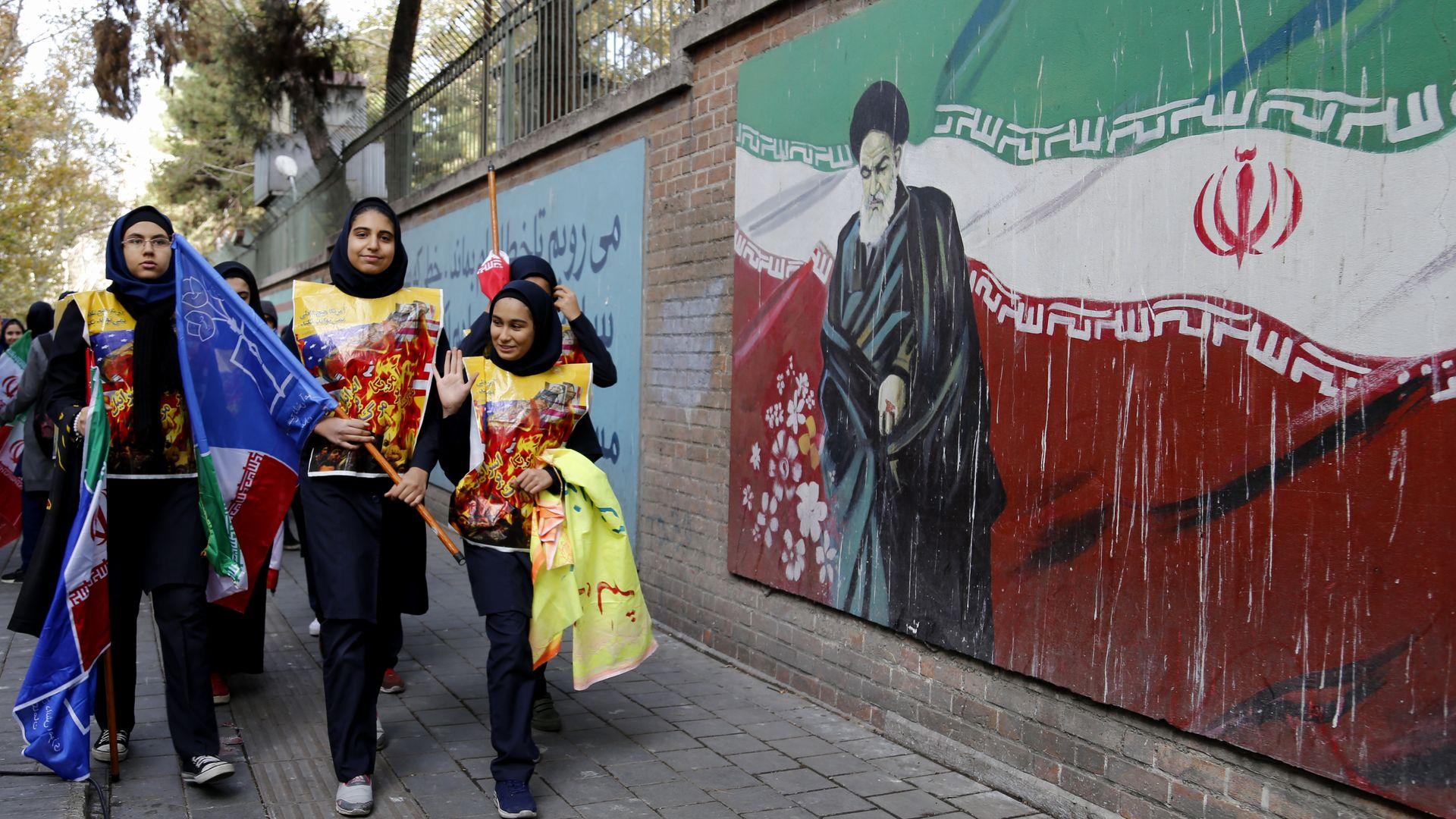 Students pass a pro-Iranian mural.