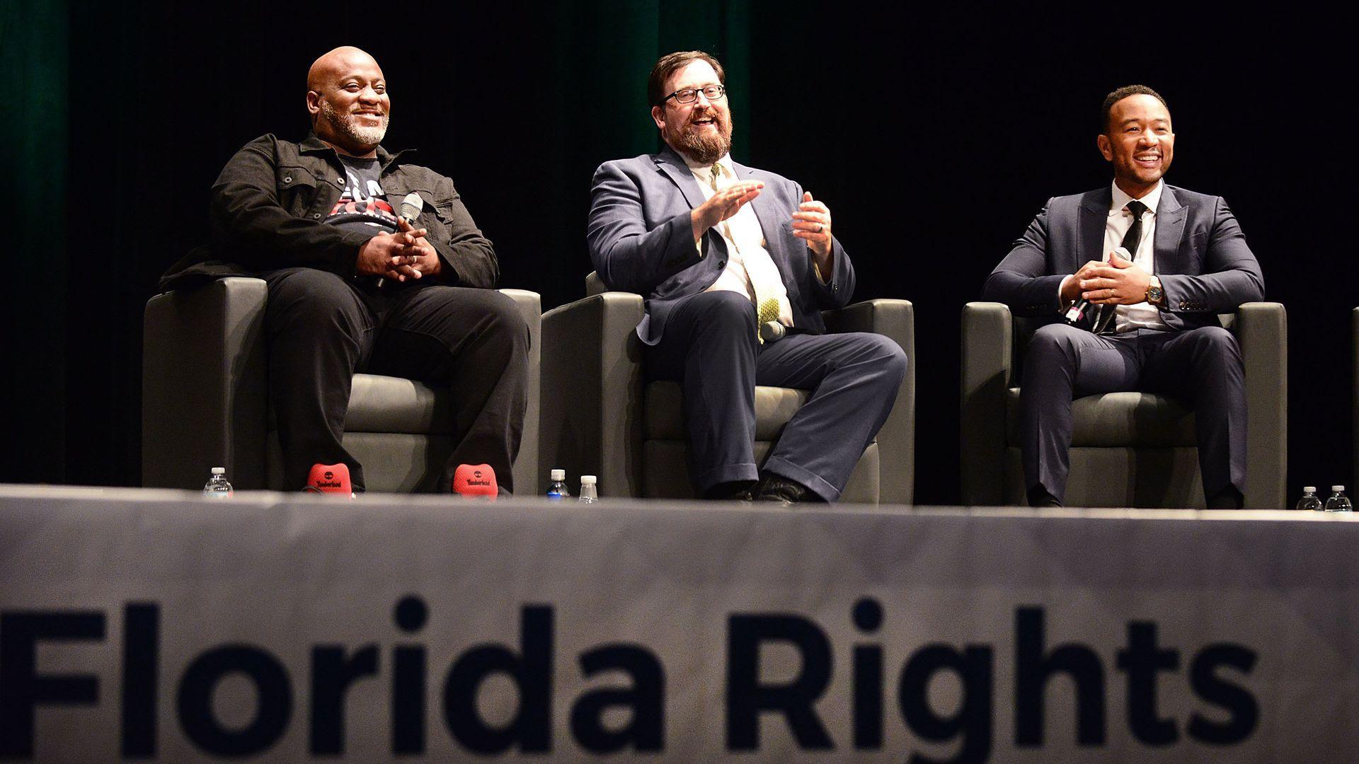 Desmond Meade (left), Neil Volz (center) of the Florida Rights Restoration Coalition and singer John Legend speak on a panel.