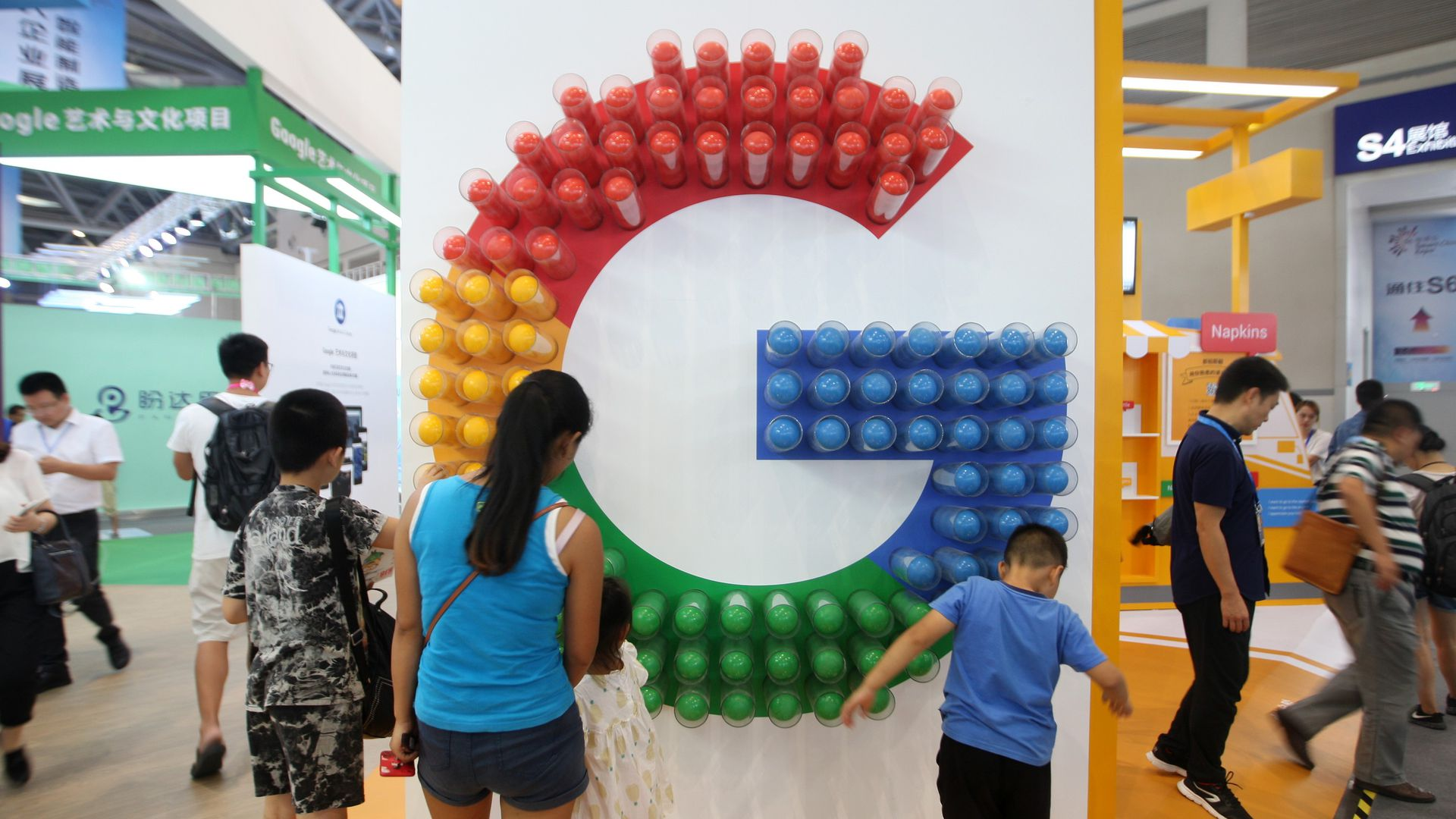 Red, yellow, green, and blue G symbolizing Google on a wall as people look on.