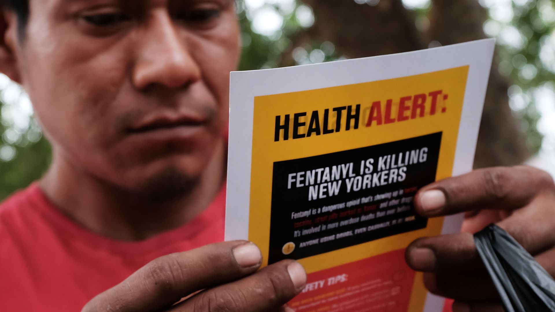 "In this image, a man holds up a poster that reads ""Health Alert: Fentanyl is killing New Yorkers"""