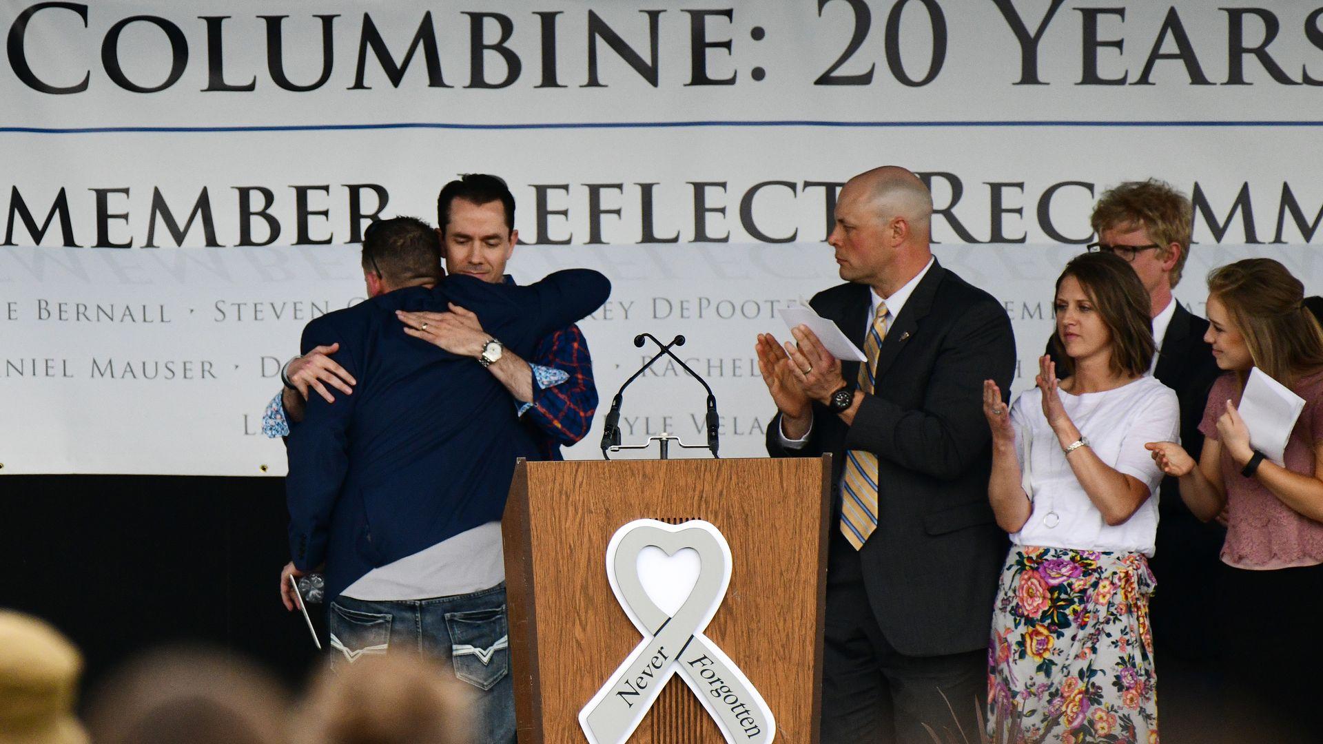 Columbine High School Shooting survivors Sean Graves, left, hugs Patrick Ireland during the Columbine: 20 memorial night.