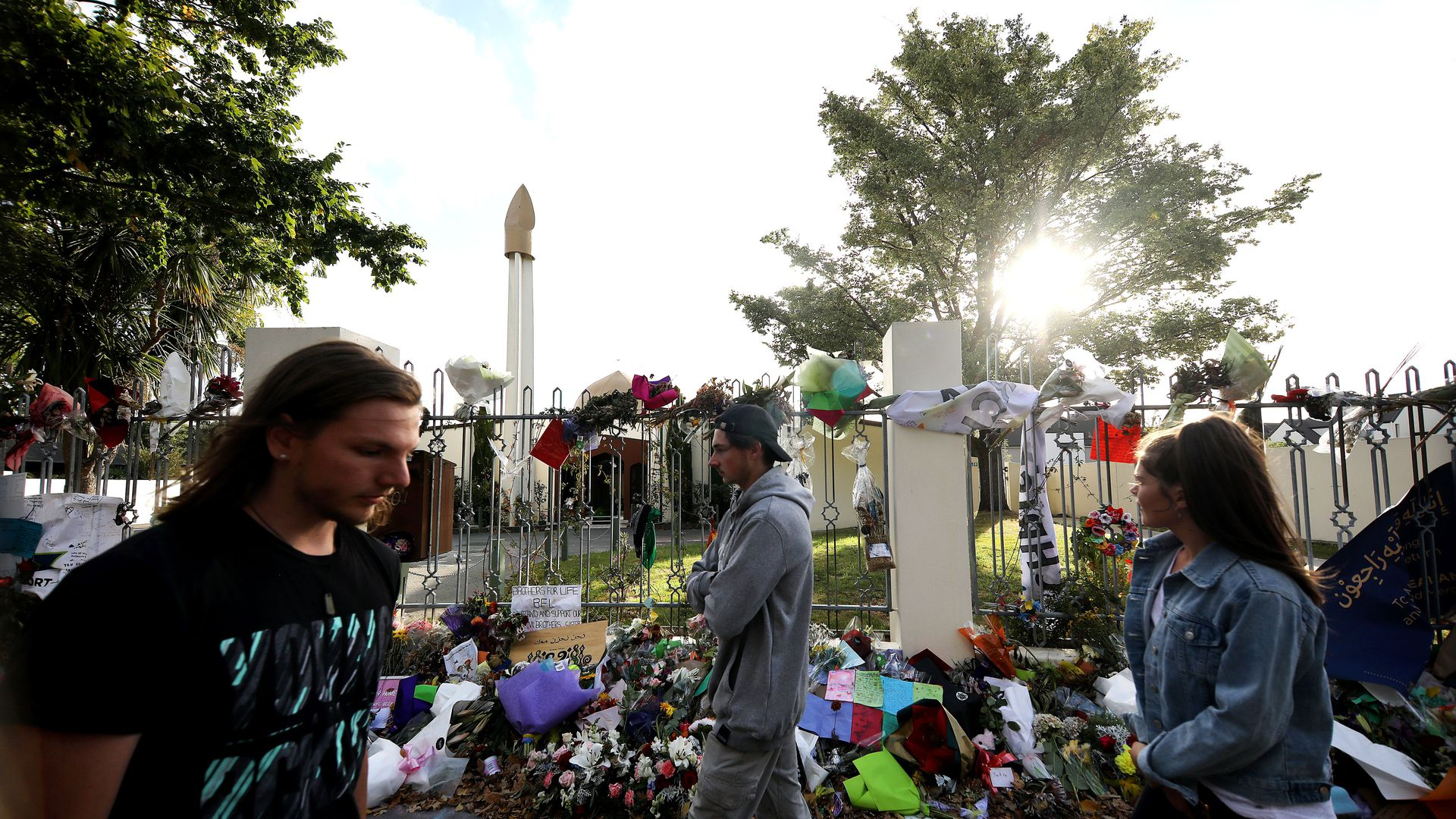 In this image, people walk by flowers and memorials laid out near a mosque fence.