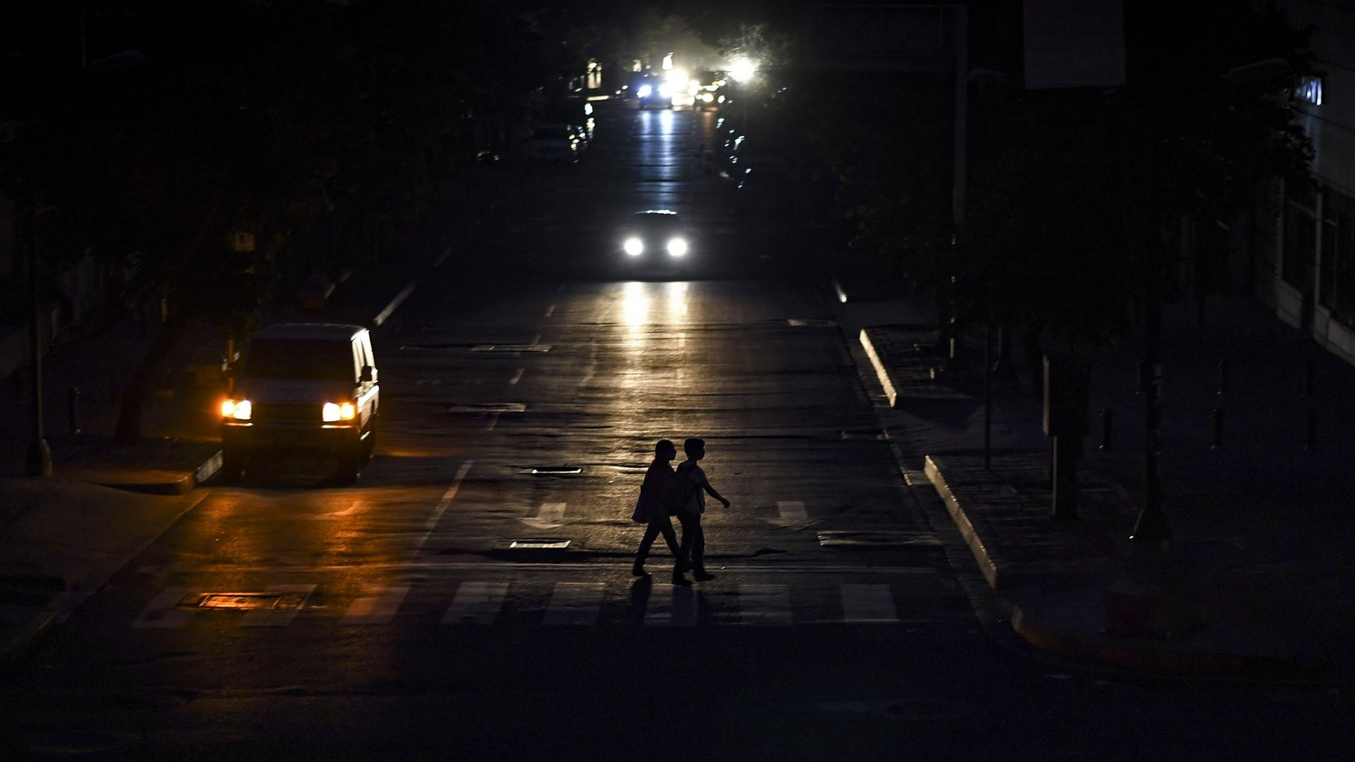 People are silhouetted by the lights of a vehicle as they cross a street in Caracas on July 22.