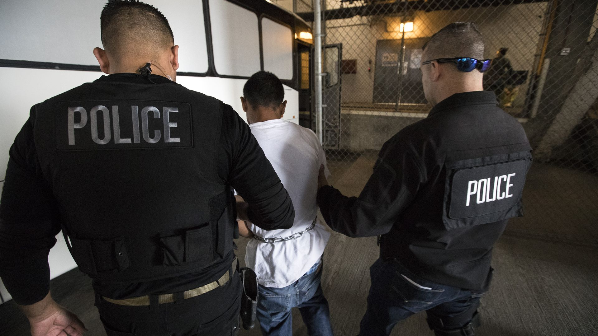 23-year-old Juan Vega, right, is escorted by agents into the ICE downtown staging facility in Los Angeles, Calif.