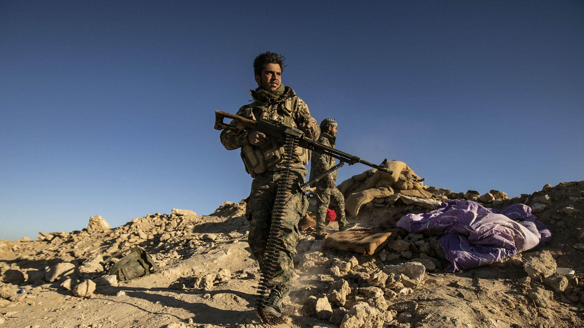 A Syrian fighter stands alone on a dirt hill, carrying an assault weapon.
