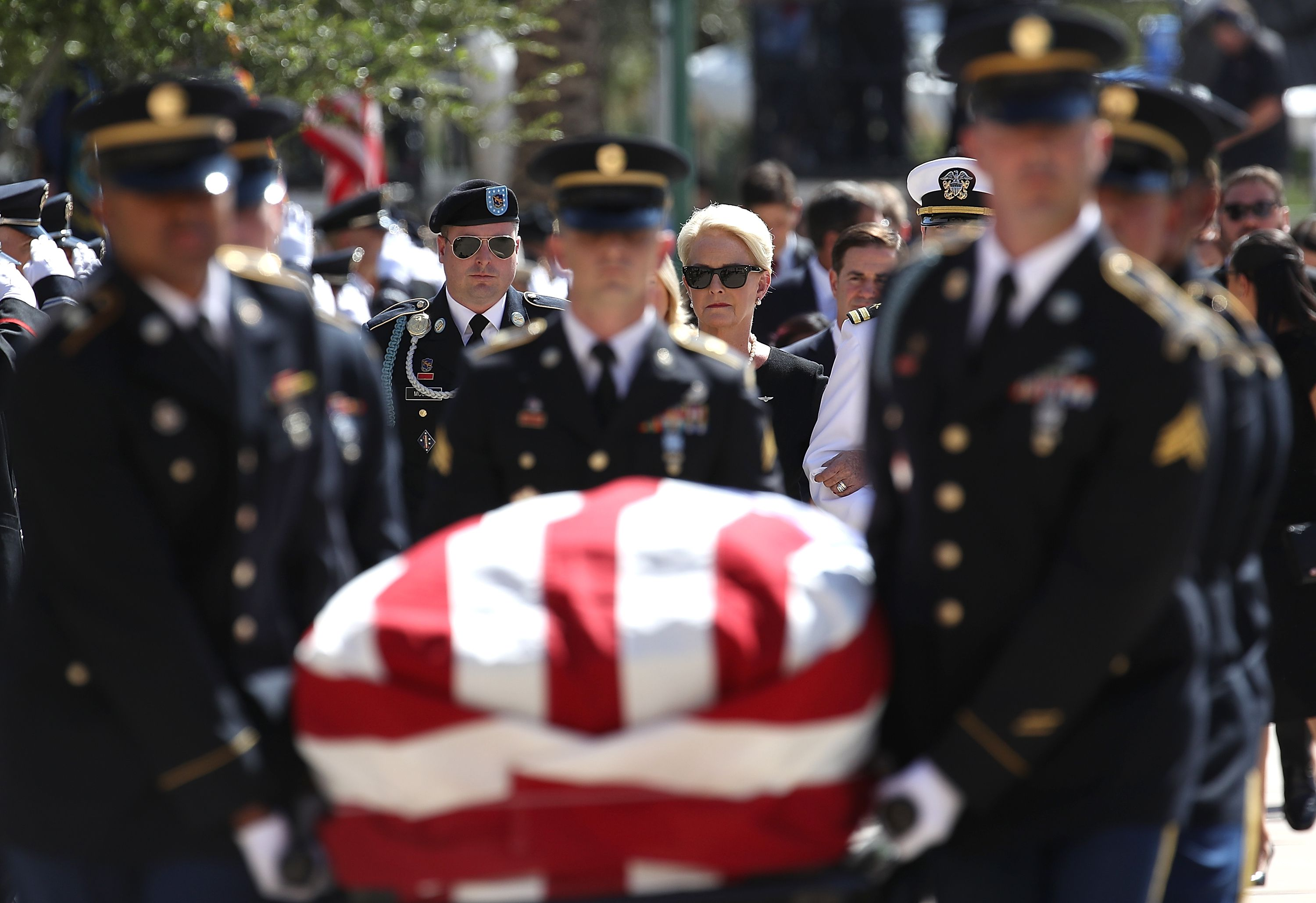McCain's casket carried in, Cindy McCain in focus behind.