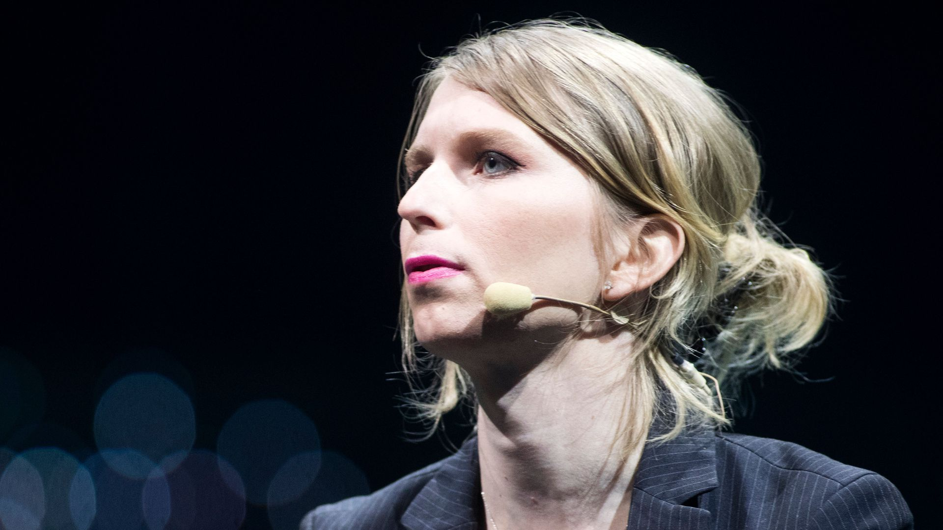 In this image, Chelsea Manning looks to the left while wearing a microphone.