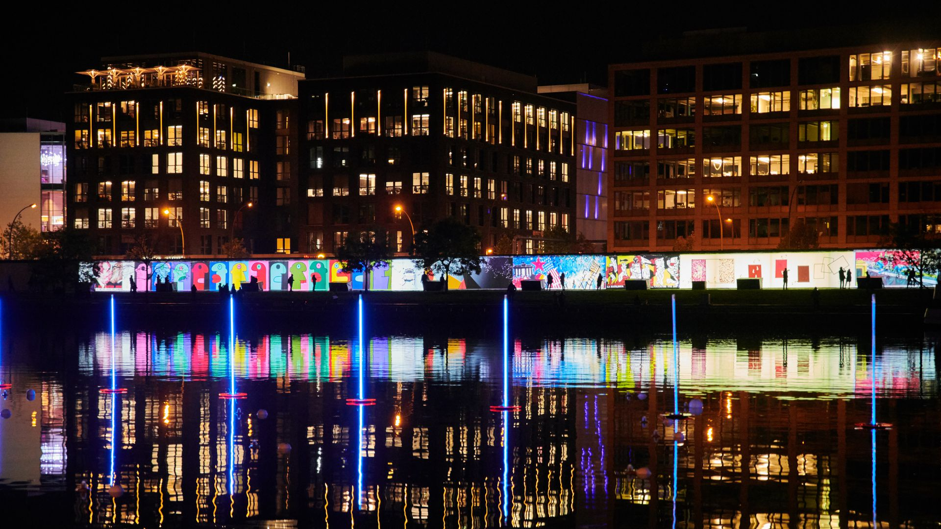 video projection onto Berlin wall with glow reflected in the Spree river