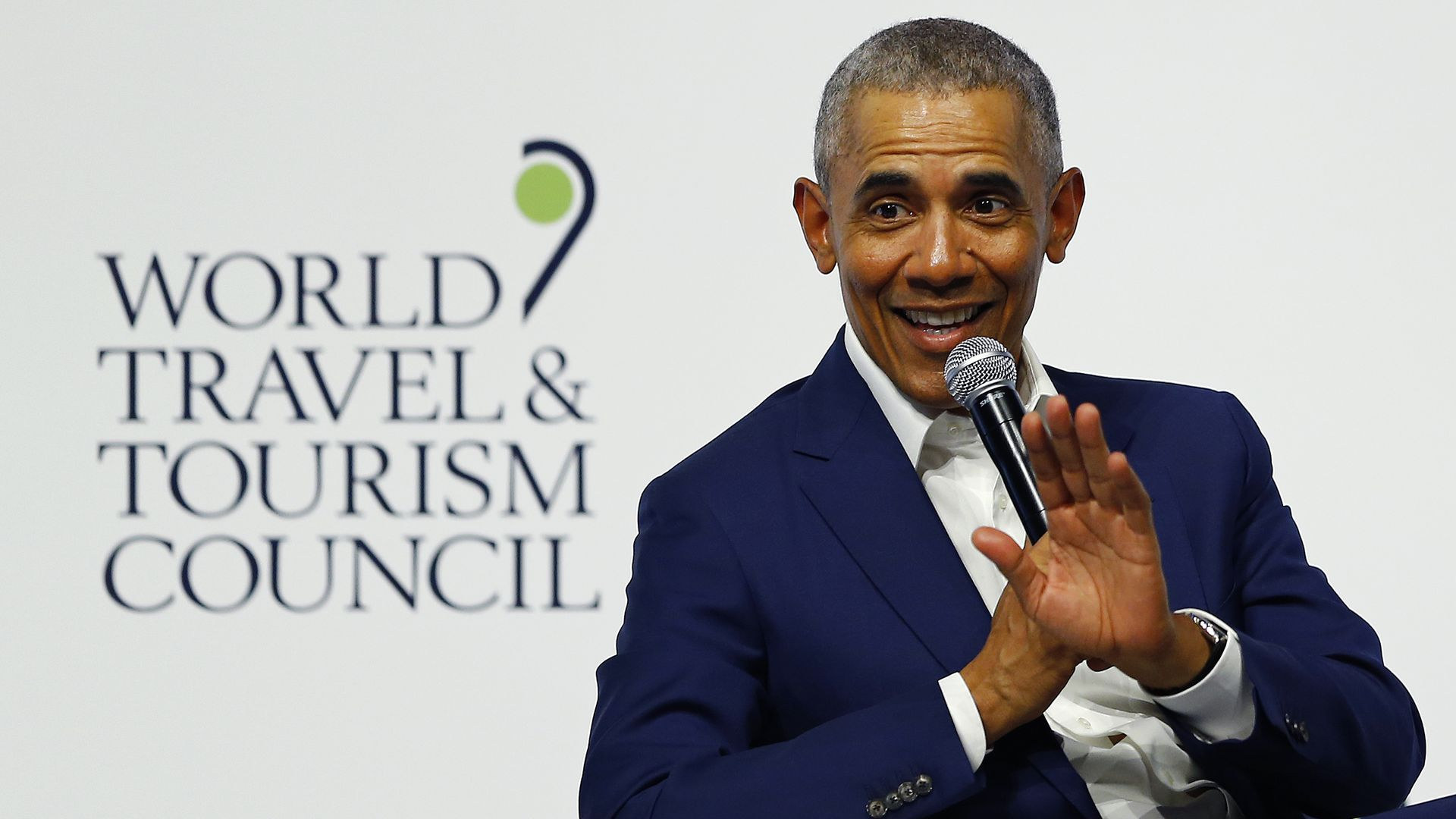 In this image, Obama sits in a chair and waves to the audience while smiling and speaking into a microphone.