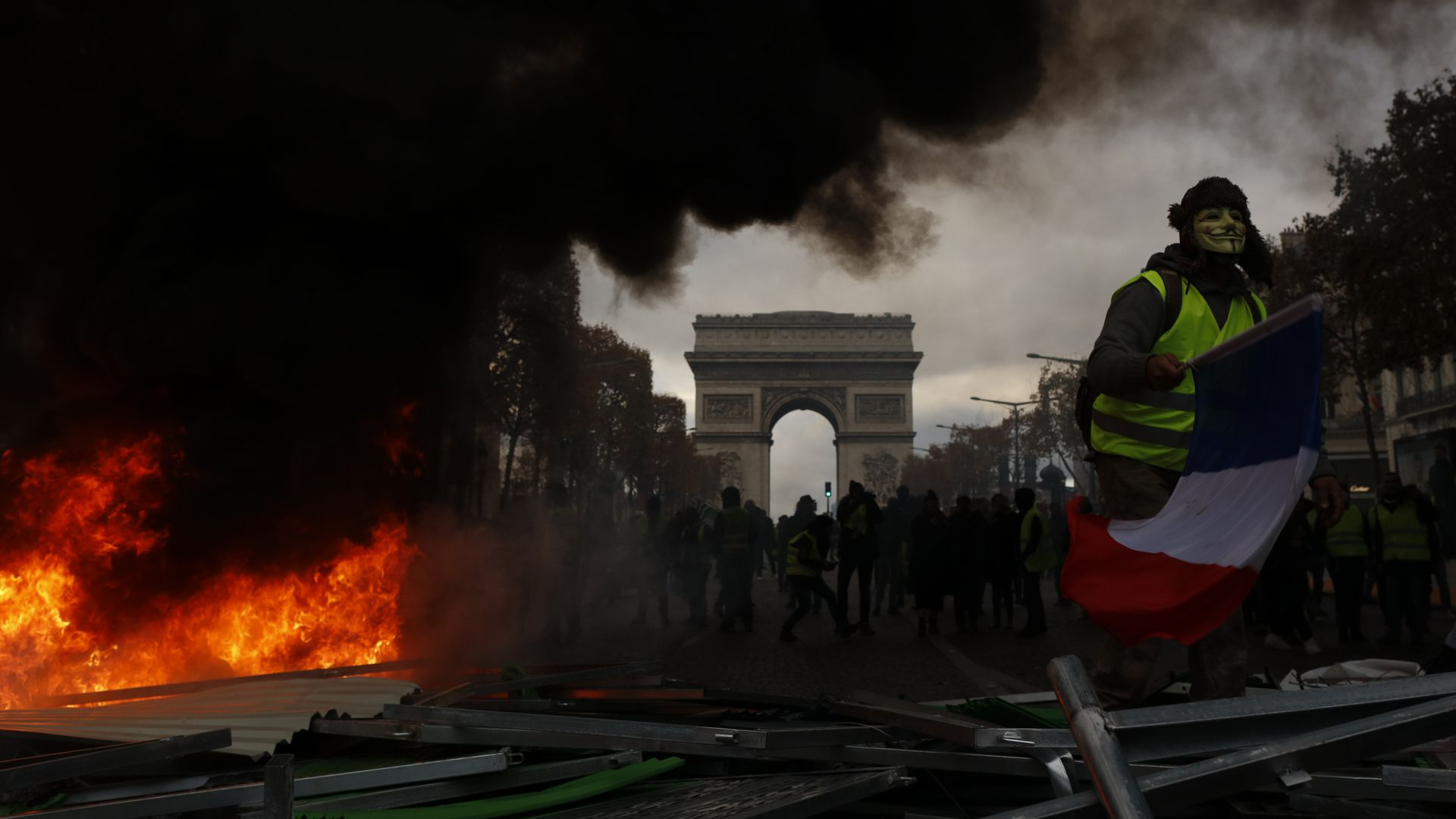 Yellow vests (Gilets jaunes) protestors shout slogans as material burns during a protest against rising oil prices and living costs near the Arc of Triomphe on the Champs Elysees in Paris
