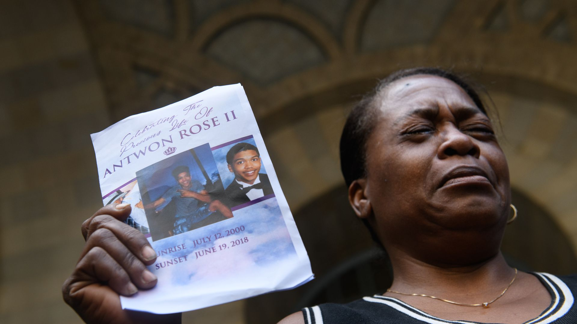 Carmen Ashley, the great aunt of Antwon Rose II, cries as she holds the memorial card from Rose's funeral in this file photo.