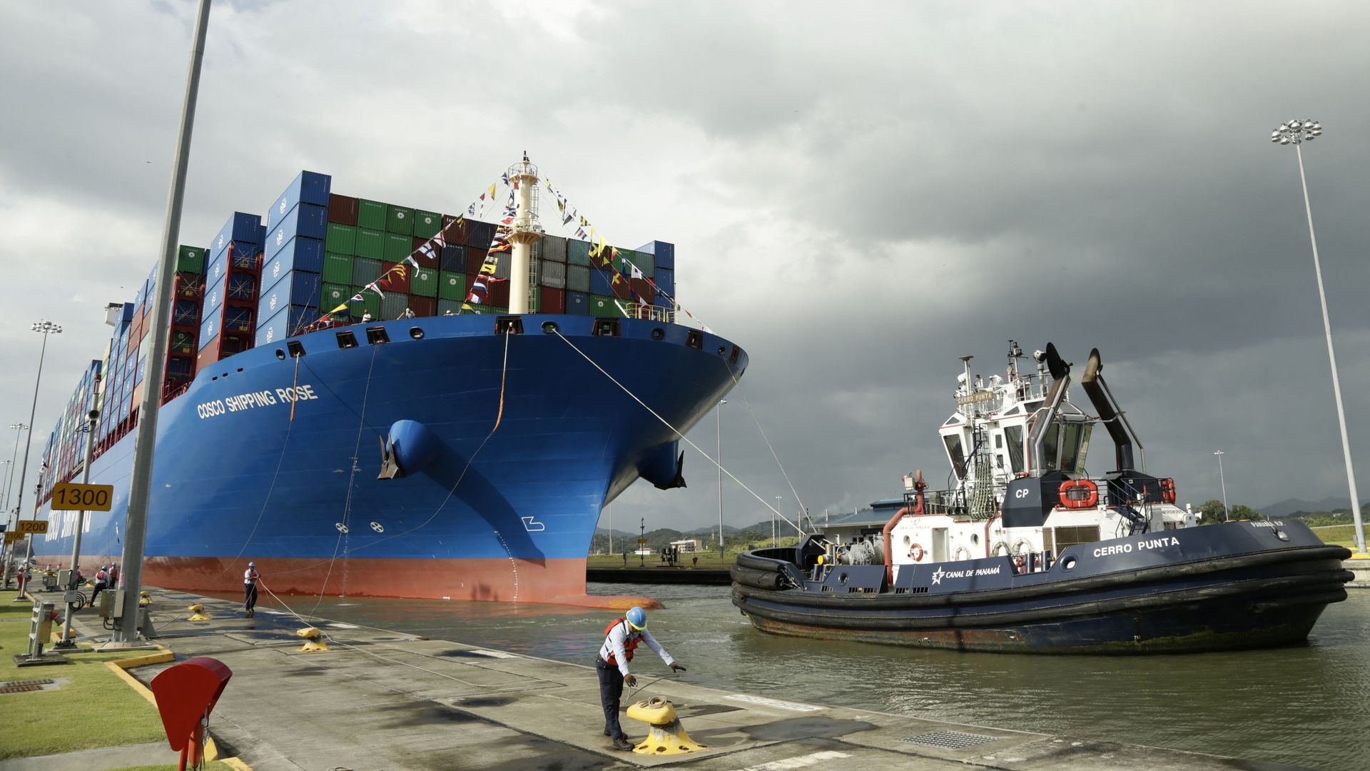 In this image, a dock worker at the Panama canal docks a huge shipping container that sits on the water.