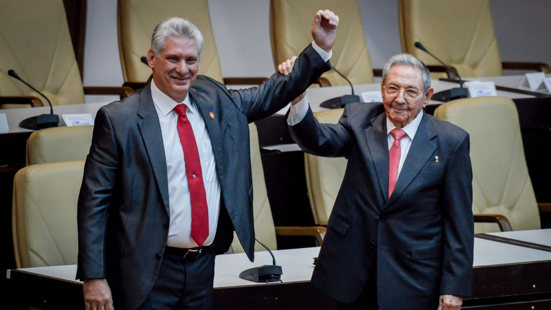 Former Cuban President Raul Castro raises the arm of newly elected Cuban President Miguel Diaz-Canel.