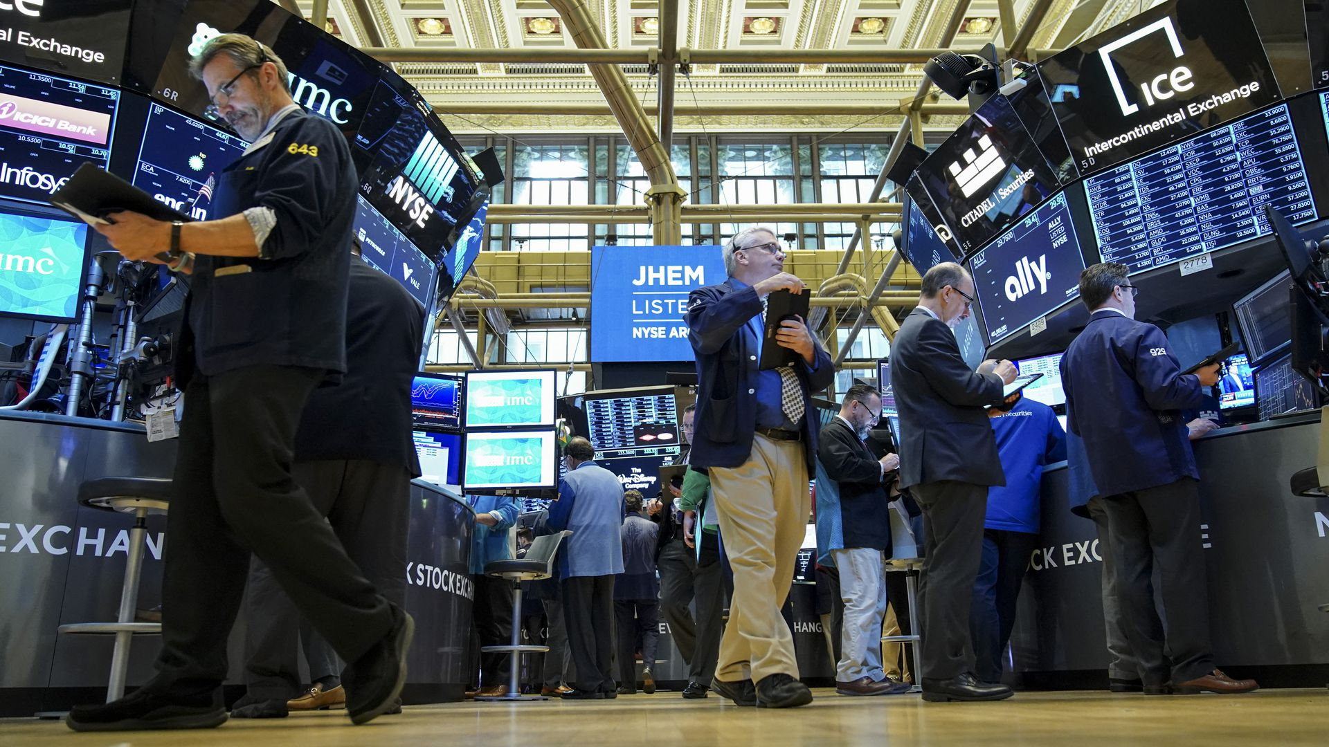 In this image, the camera looks up from the New York Stock Exchange floor as men walk across the floor and look at screens.