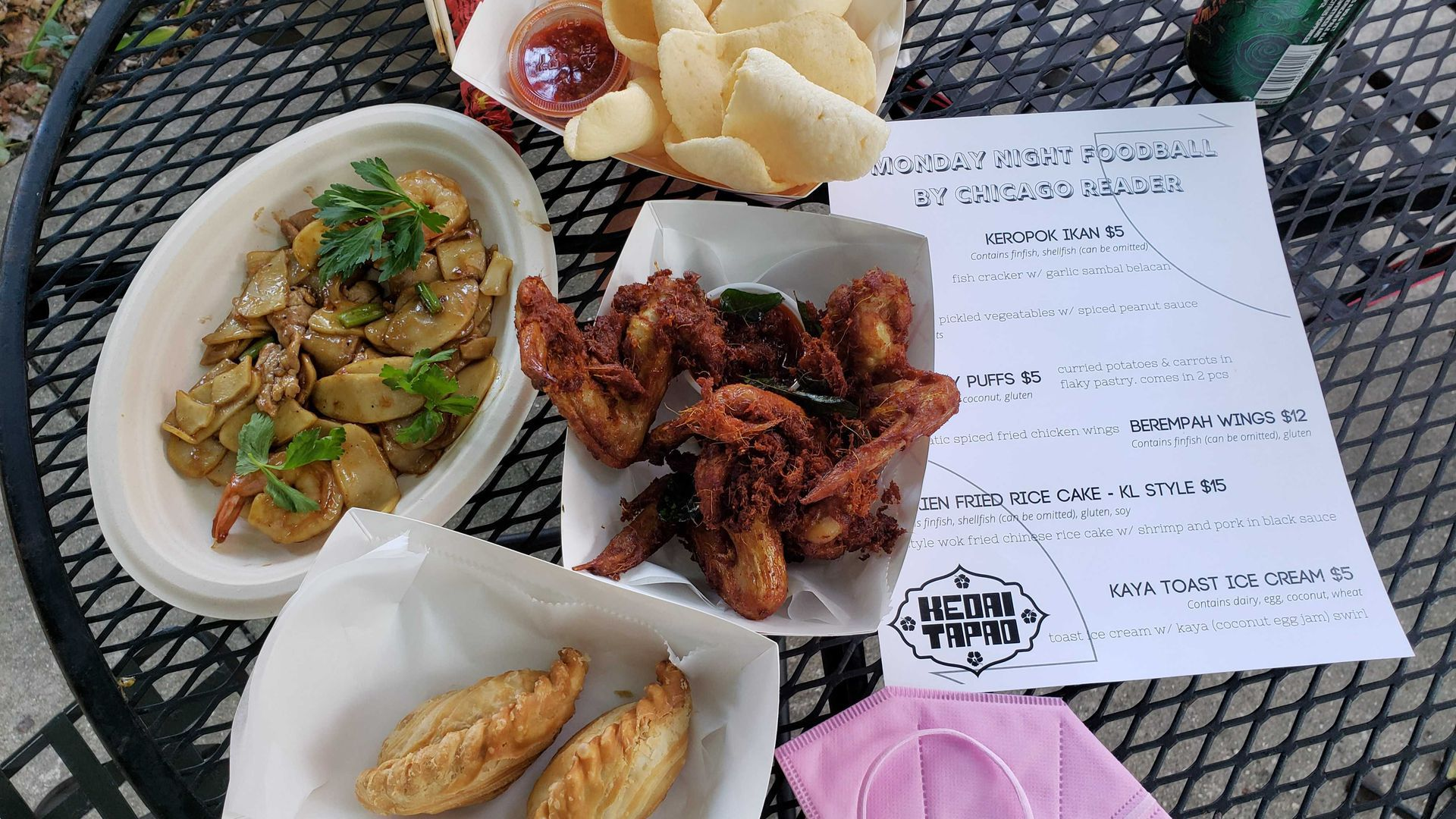 An assortment of food including Malaysian fish crackers, aromatic chicken wings, curry puffs and Hokkien rice cakes on a table.