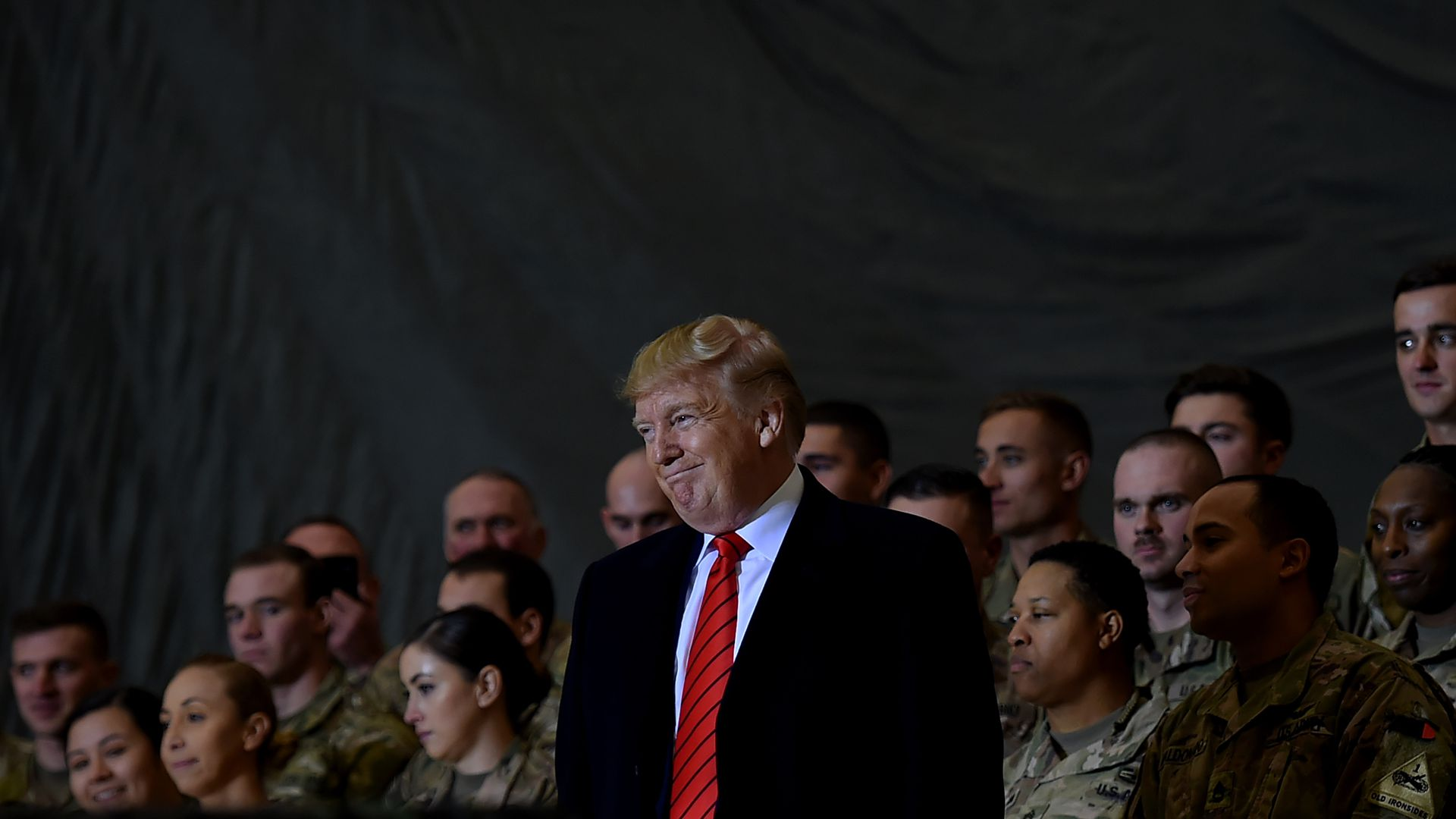 In this image, Trump stands in front of a few rows of soldiers.