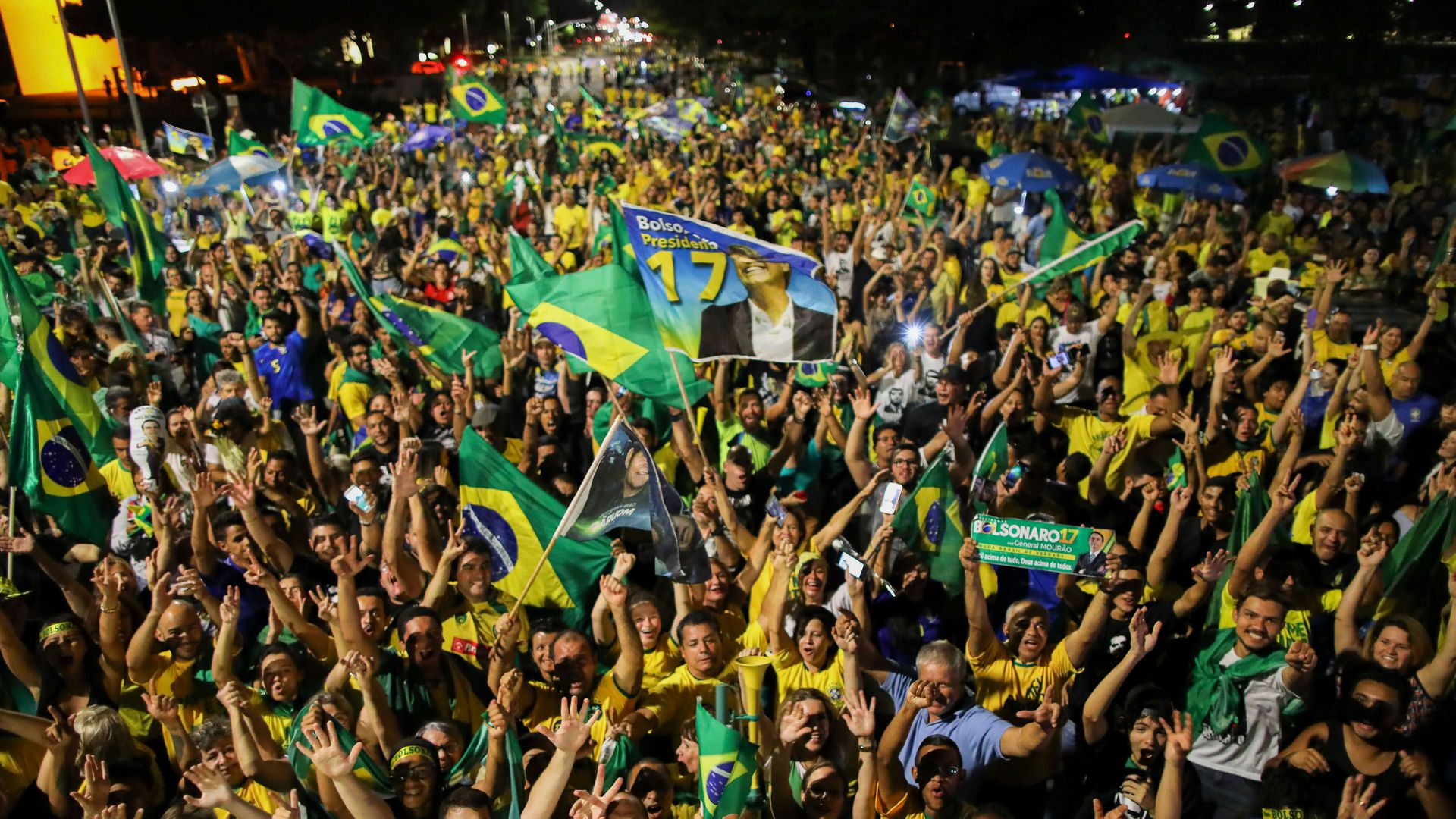 Crowd of cheering people holding Brazilian flags