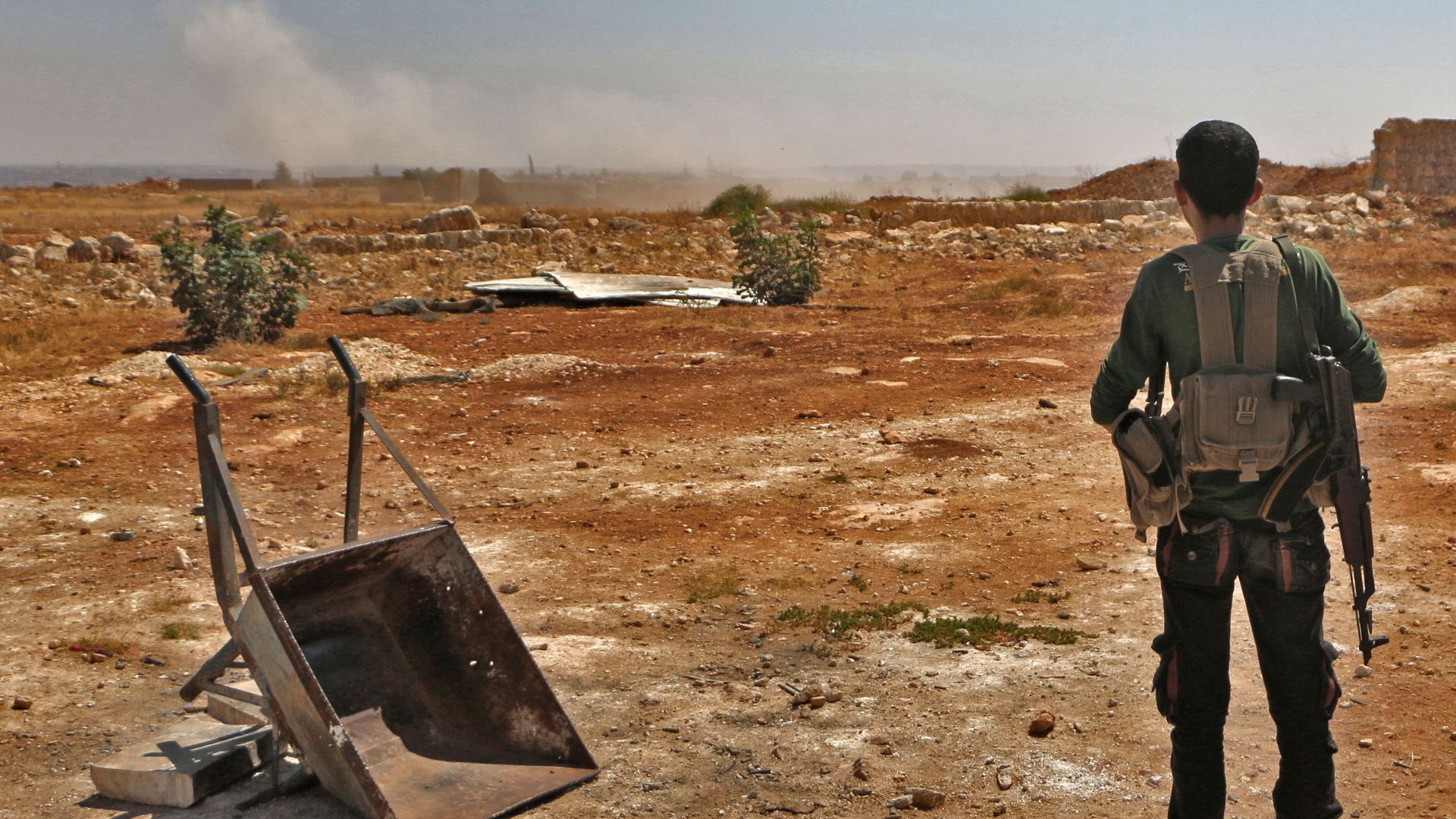 A Syrian rebel fighter holding a gun looks out onto empty land.