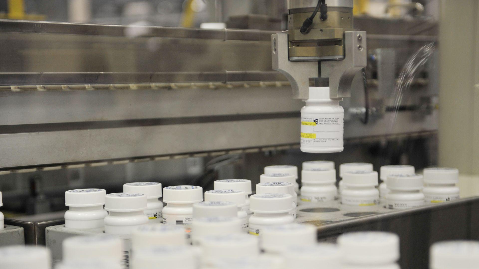 A robot arm picks up a bottle of pills.