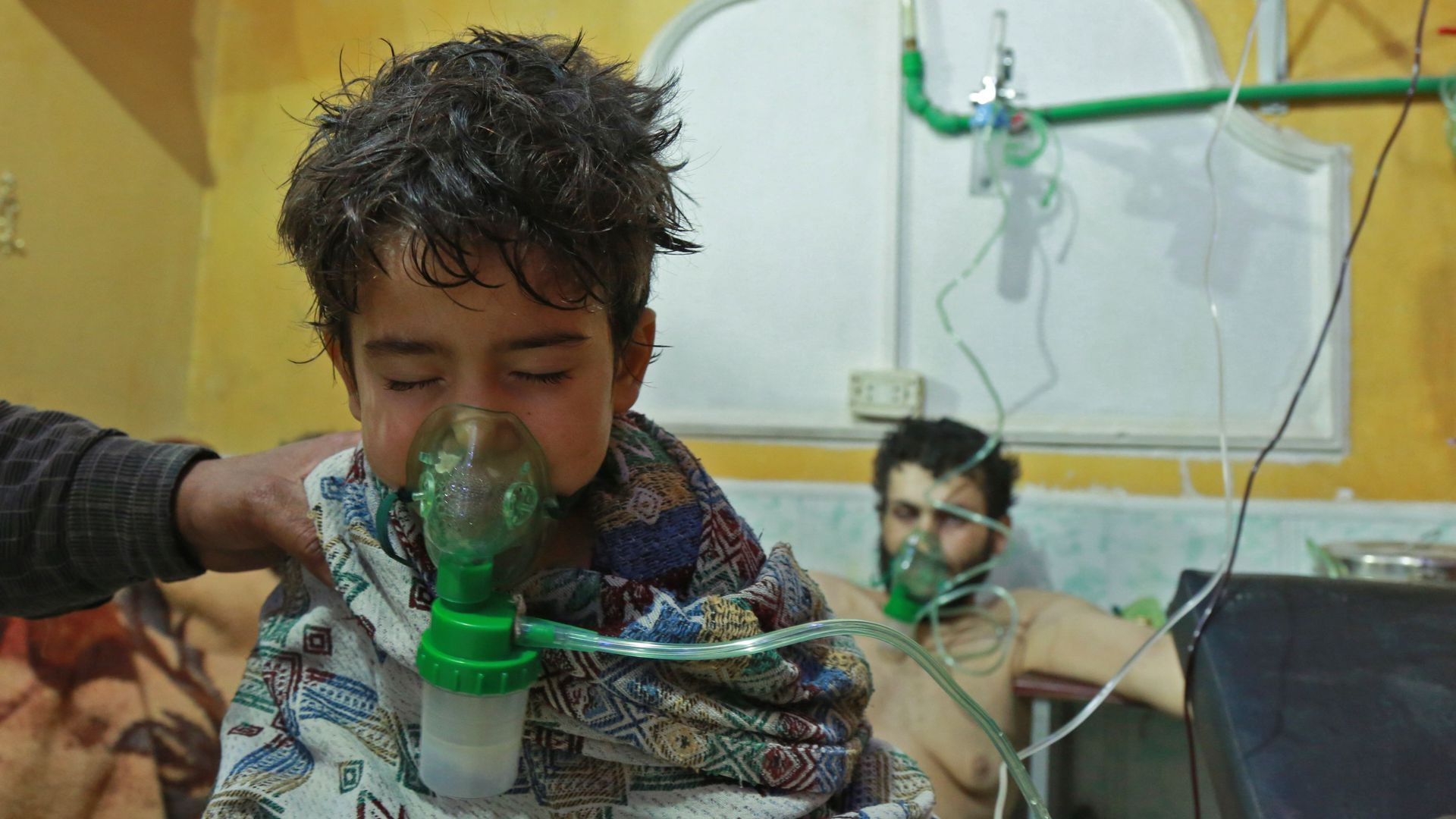 A child uses a green oxygen mask, while wrapped in a patterned blanket. A min sits behind him using a mask too. The wall is yellow.