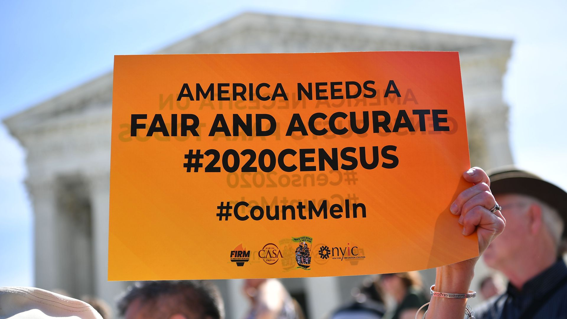 A protester hoists a sign calling for a fair and accurate 2020 Census on the steps of the U.S. Supreme Court at an April rally.