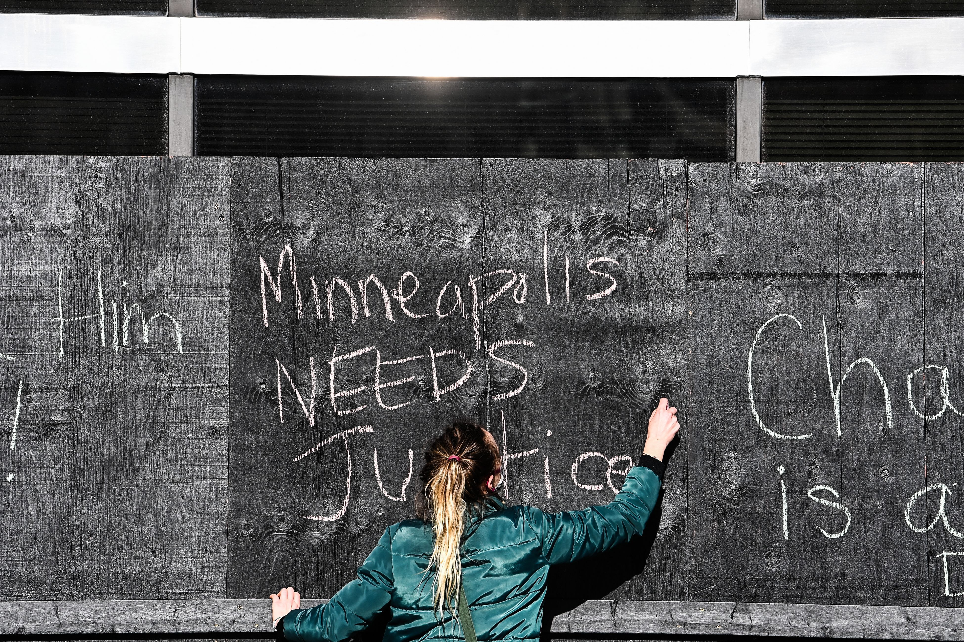 A woman writes a message for justice in chalk