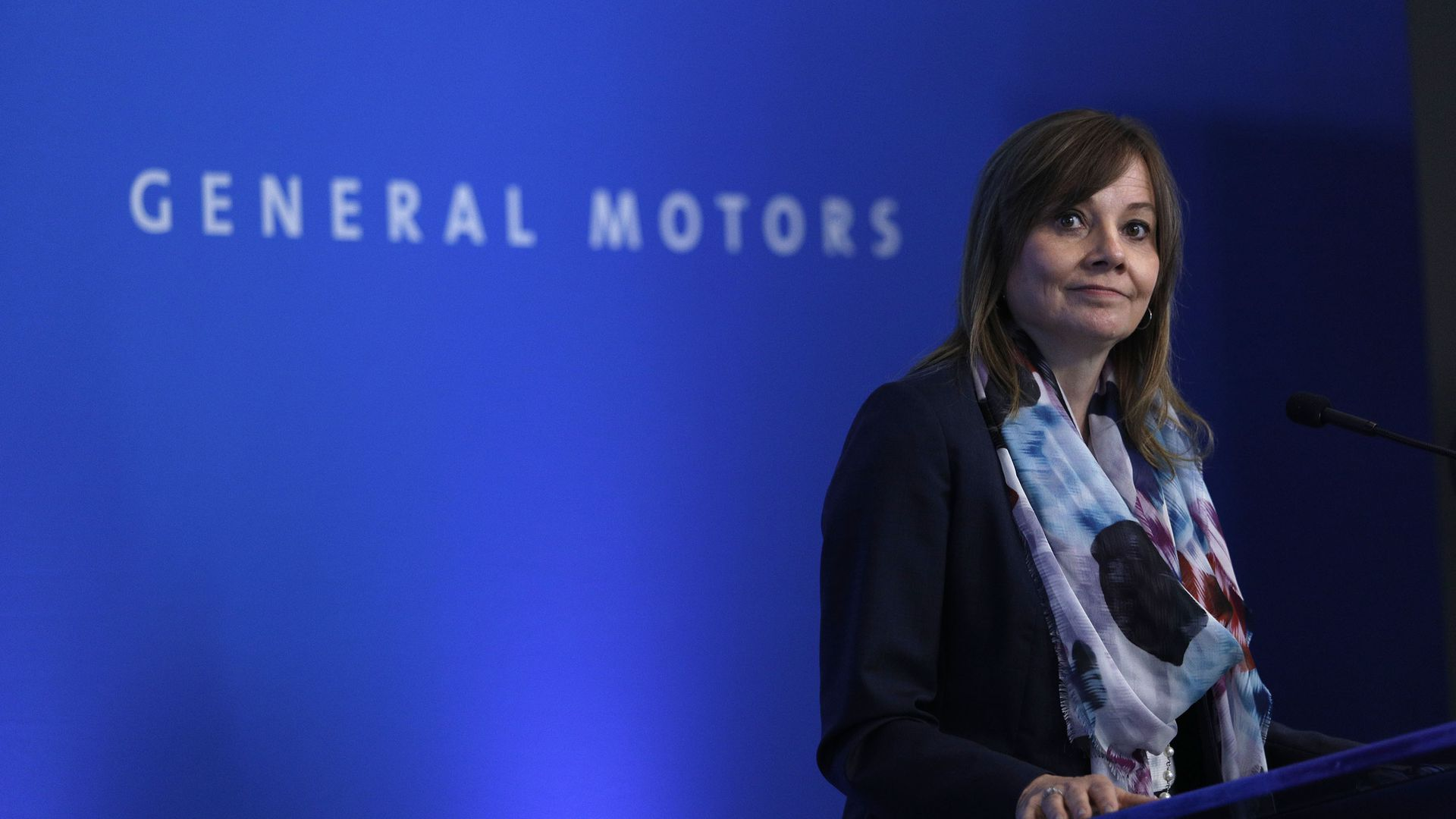 "General Motors CEO Mary Barra speaks in front of a blue backdrop with white letters that spell ""General Motors"""