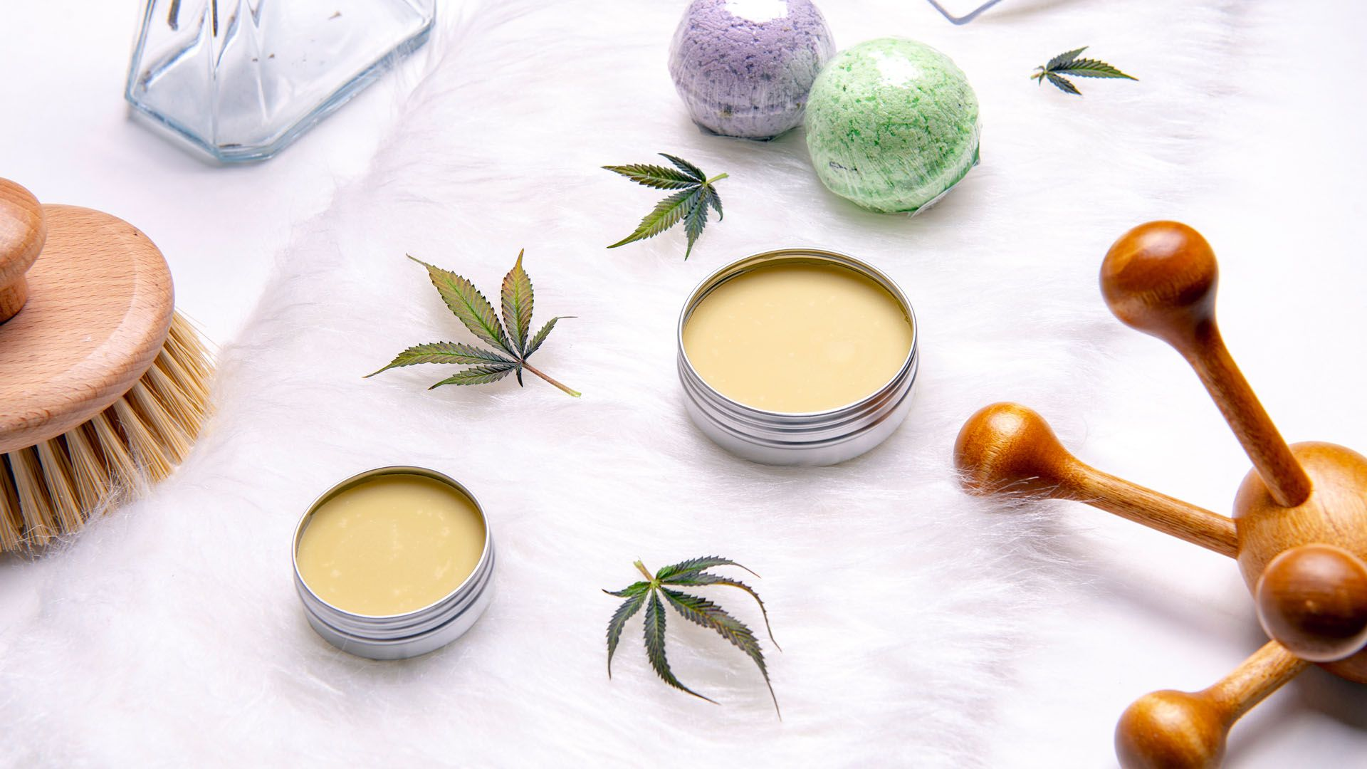 Several lip balms arranged in a pleasing pattern next to cannabis leaves