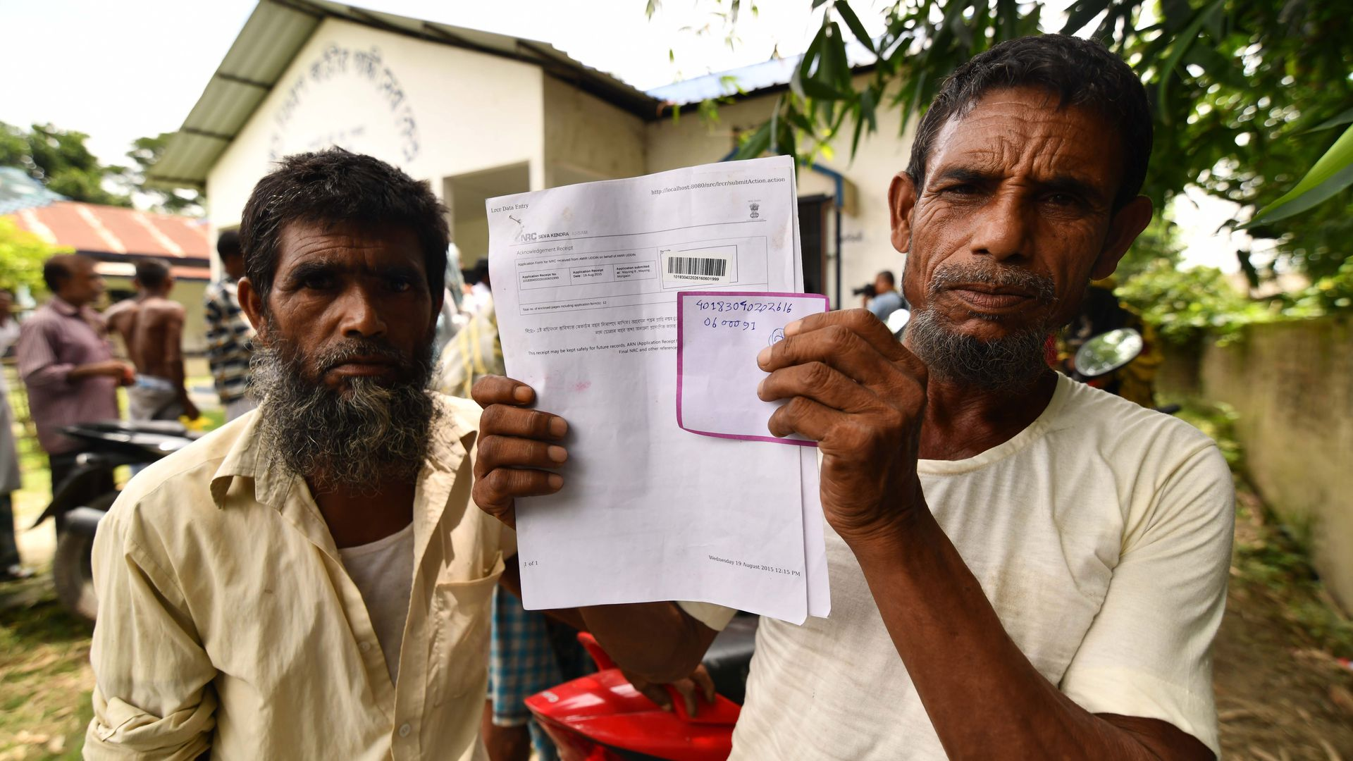Resident of Assam holding up his citizenship papers