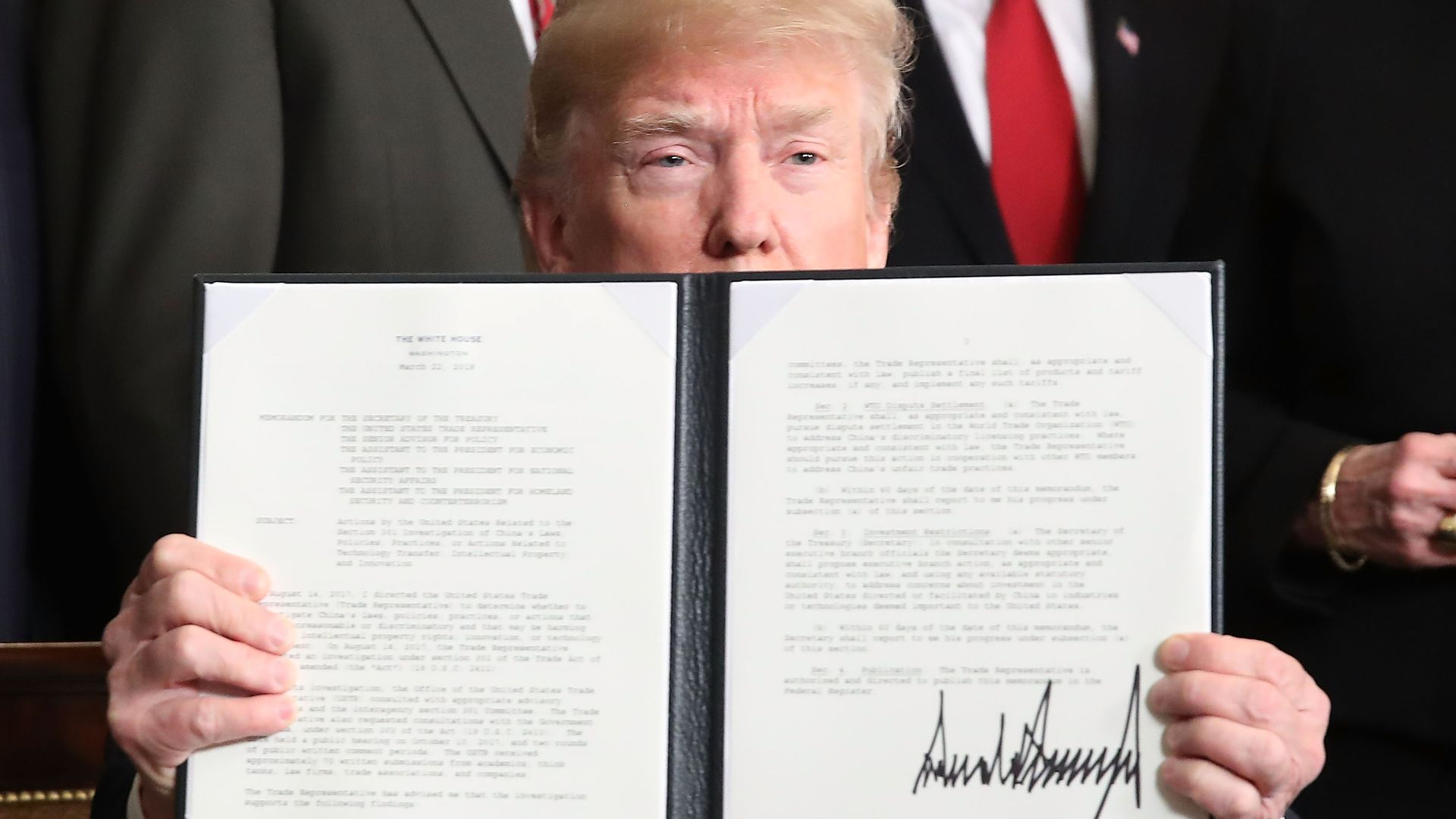 U.S. President Donald Trump holds up a signed presidential memorandum aimed at what he calls Chinese economic aggression in the Roosevelt Room at the White House.