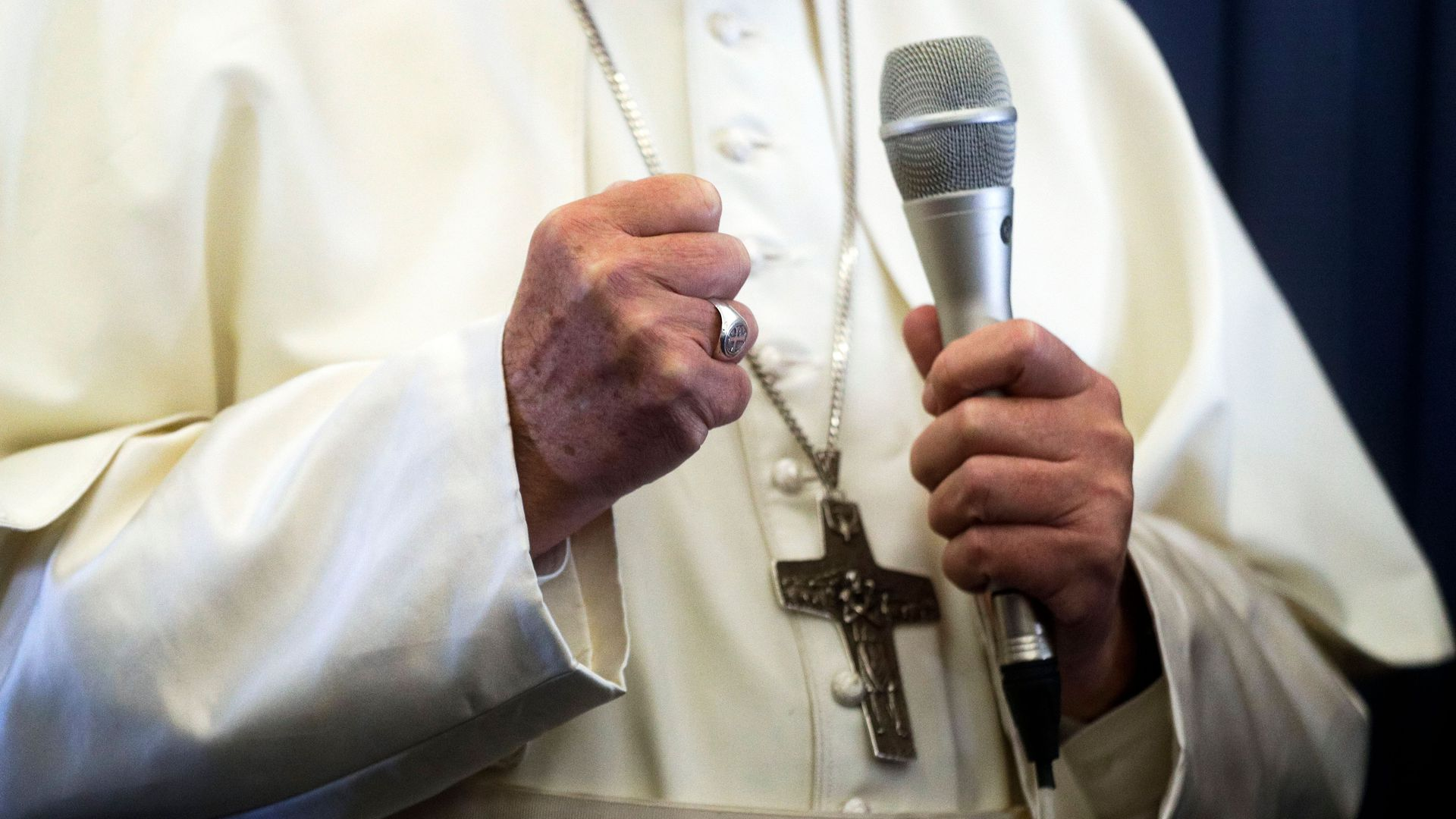 A shot of the pope's hands and robes, but not his face. One hand is in a fist, one hand holds a microphone. A crucifix necklace hangs on his white robes.