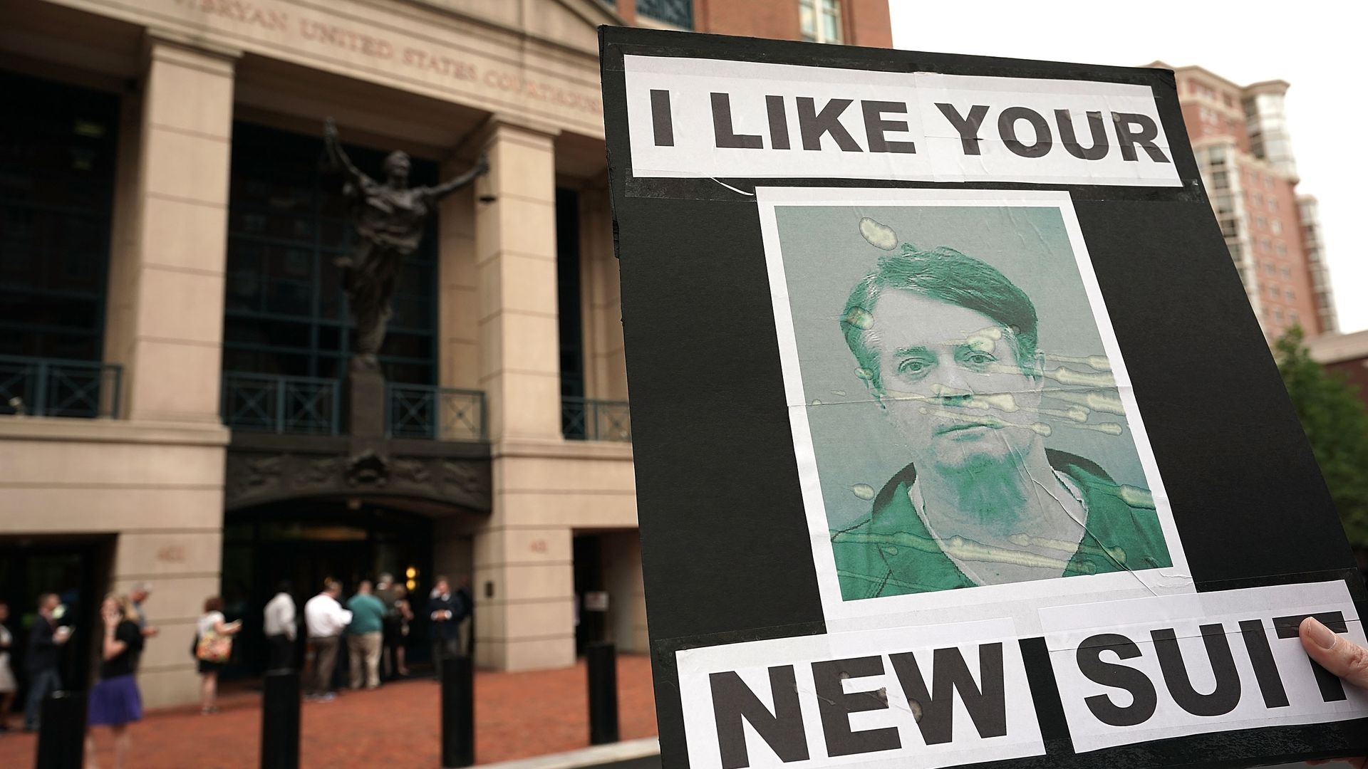 """An activist holds a sign with a photo of Paul Manafort's mug shot, that reads: """"I like your new suit."""""""