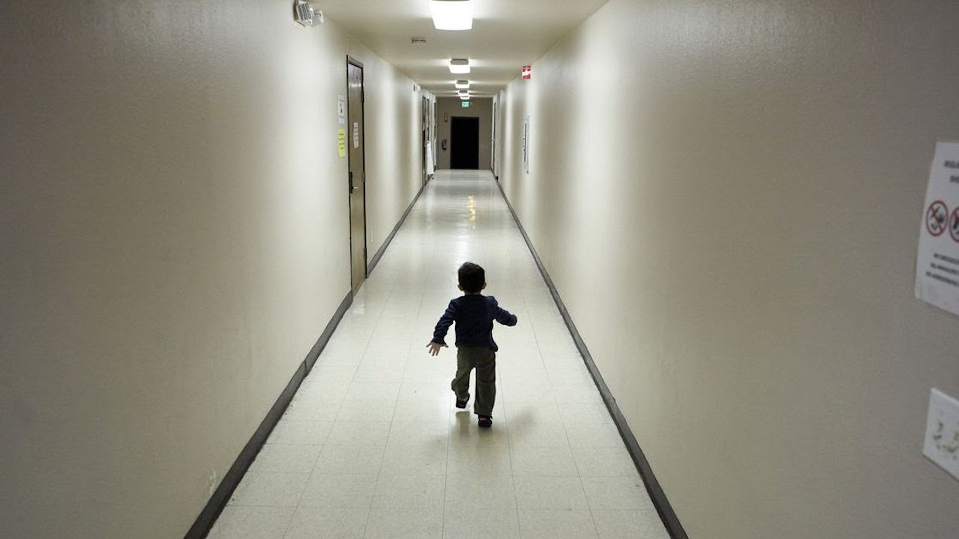 A child running down an empty hallway