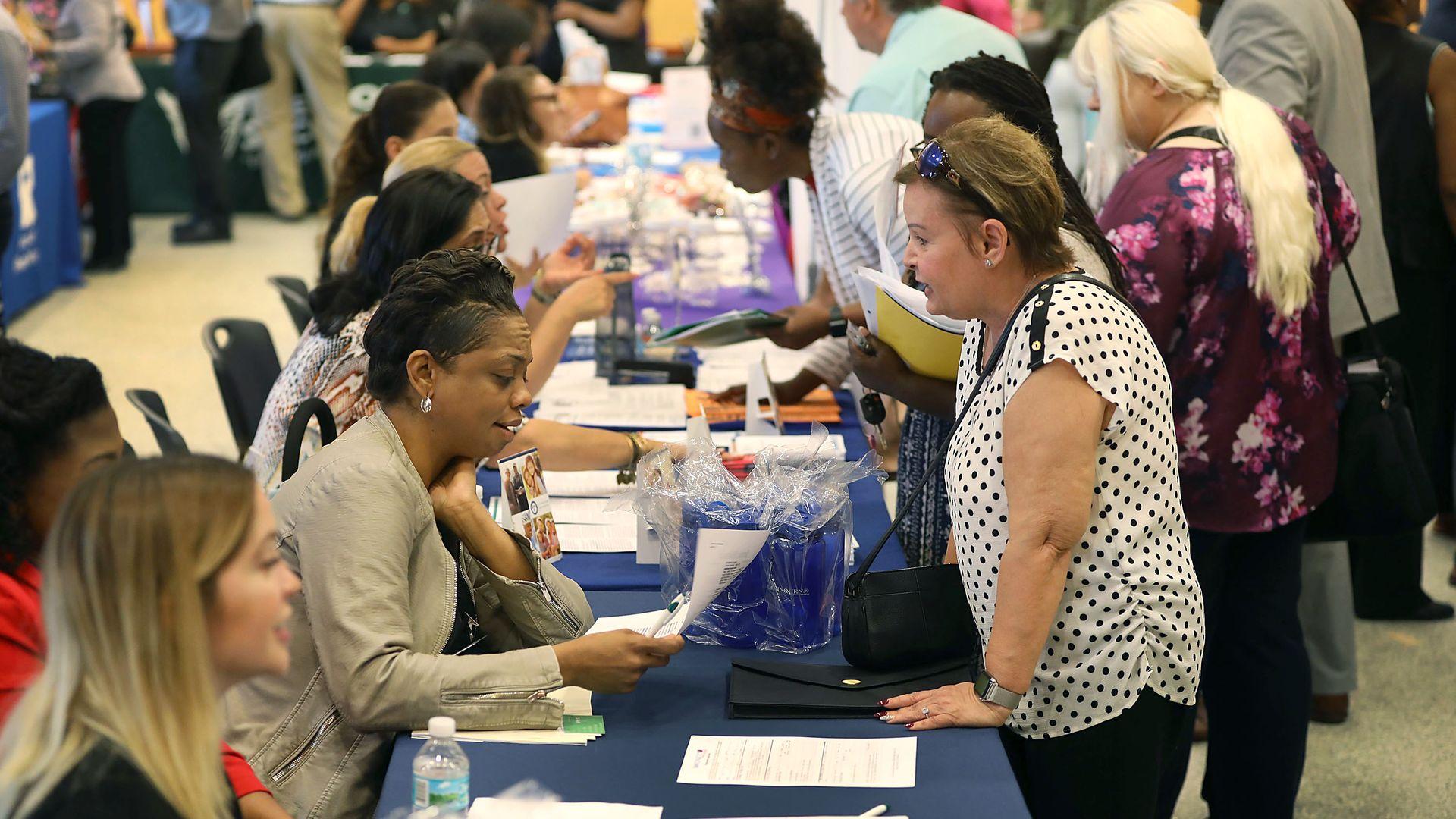 People attend a job fair in Miami, Fla., in April 2019.